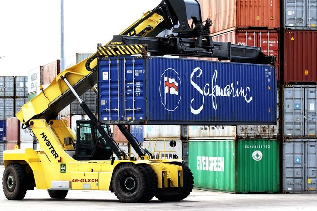 A heavy lifting machine carrying a cargo or shipping container in a freight yard at the docks. Shipping Containers Cargo Container Export Import Industry Lifter Trade Docks Dock Logistics Shipping Terminal Rail Container Machines Machine Goods Freight Heavy Equipment Machinery Stacking Stacker