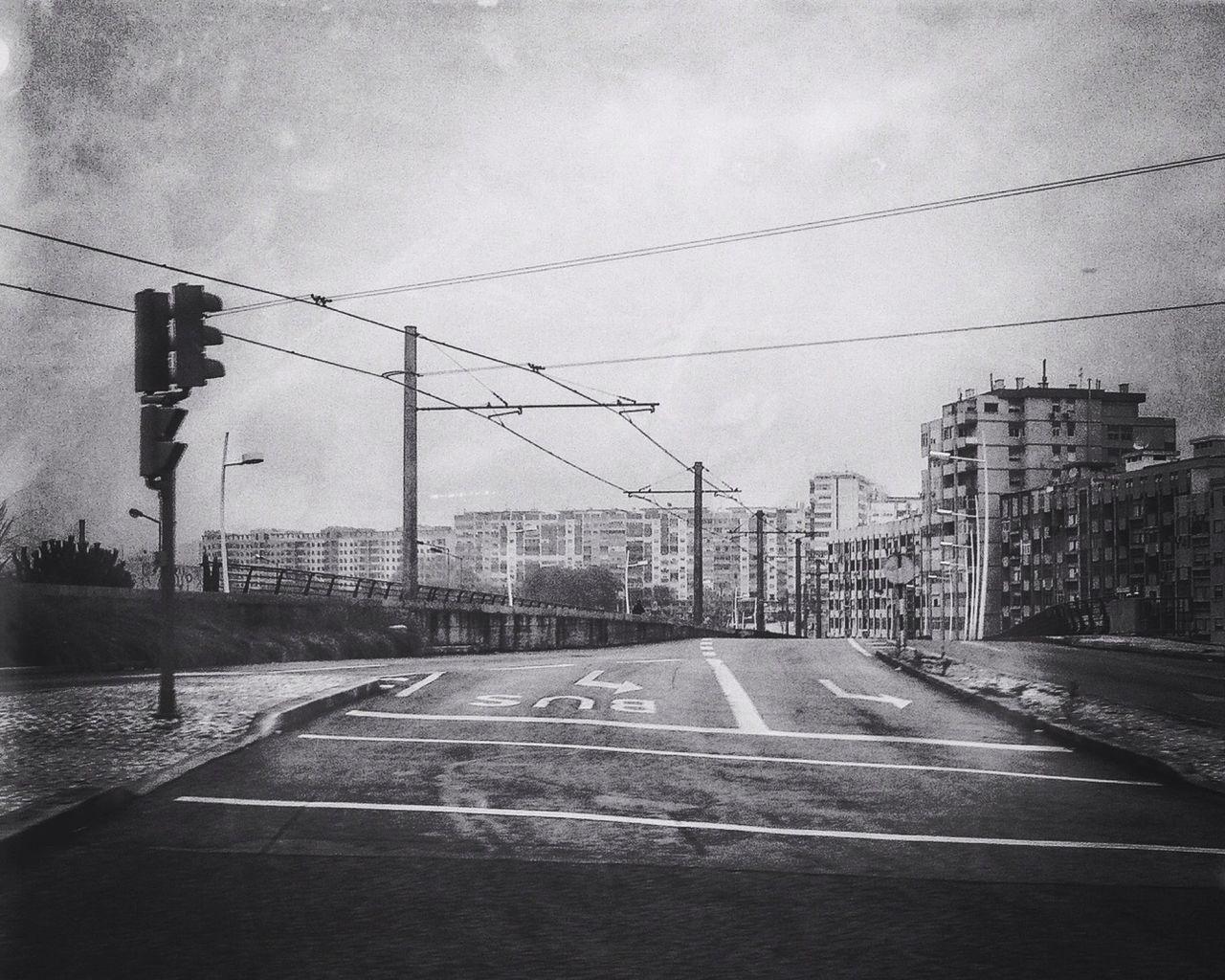 Street Leading Towards City Against Sky