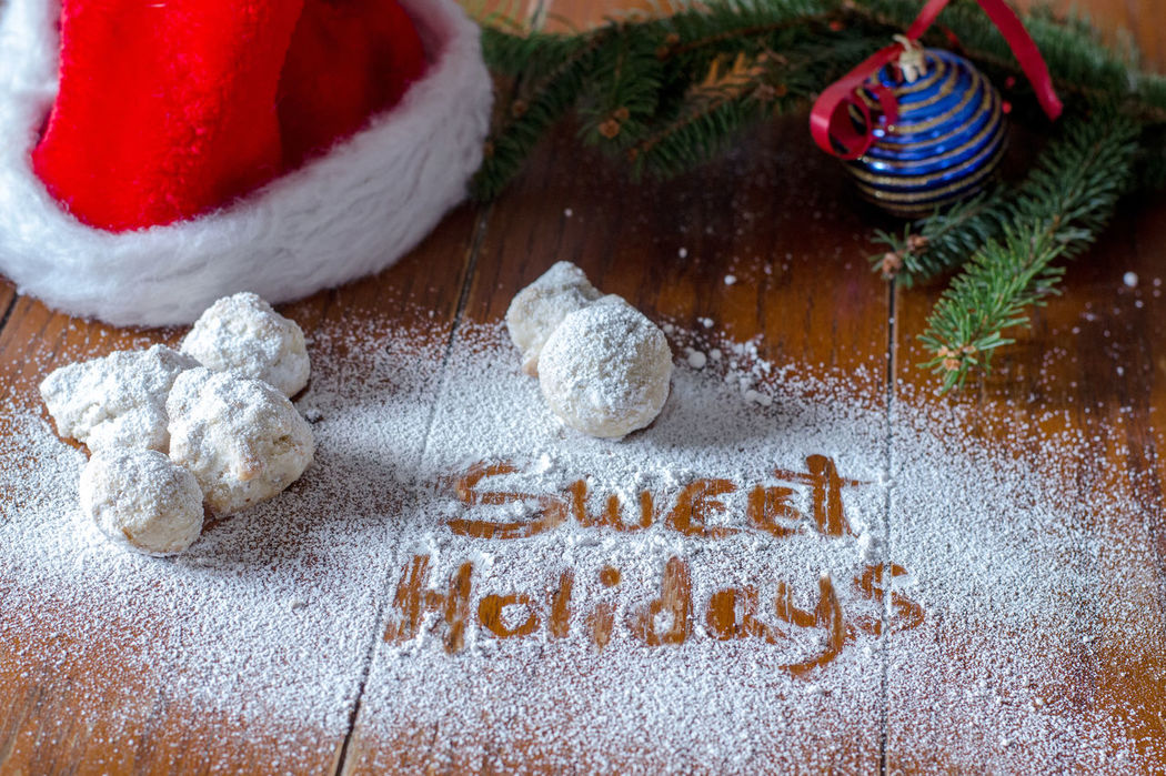 sweet treats with sweet holidays written in powdered sugar Baking Time Holiday Home Cooking Mexican Wedding Cookies Seasonal Food Sugar Calories Celebration Christmas Close-up Cookie Day Decorations For Xmas Evergreen Branches Food Food Photography Freshness Home Made Sweets  Indoors  No People Powdered Sugar Sweet Food Sweet Foods