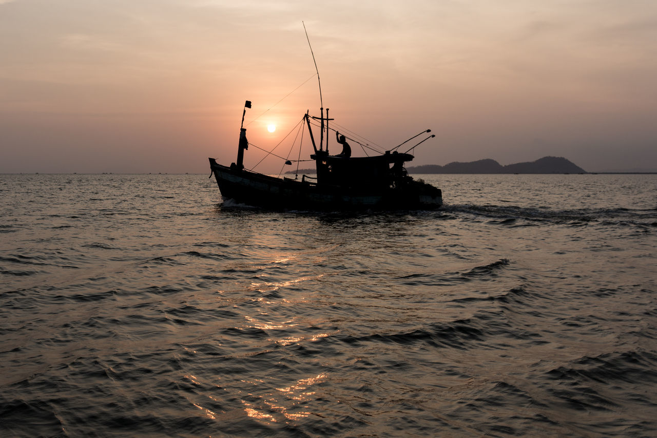 A silhouetted wooden fishing boat heads out to sea at sunset with island background. Calm Centre Direction Fishing Fishing Boat Island Nautical Vessel Ocean Outdoors Sailing Sailing Ship Sea Silhouette Single Sky Sunset Sunshine Transportation Vessel Water Work