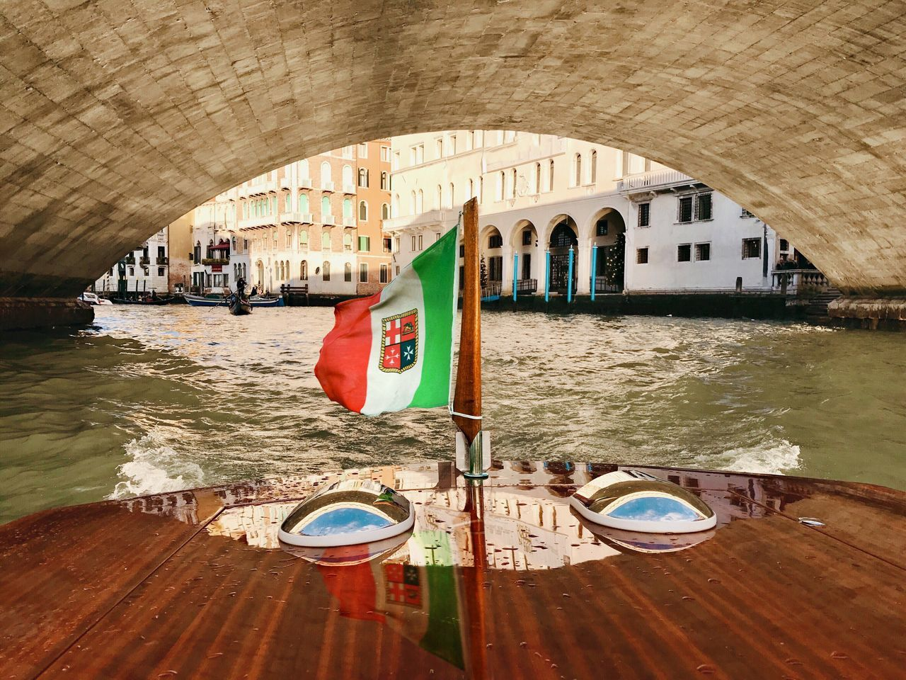 Italian Flag On Water Taxi Under Arch Bridge In River