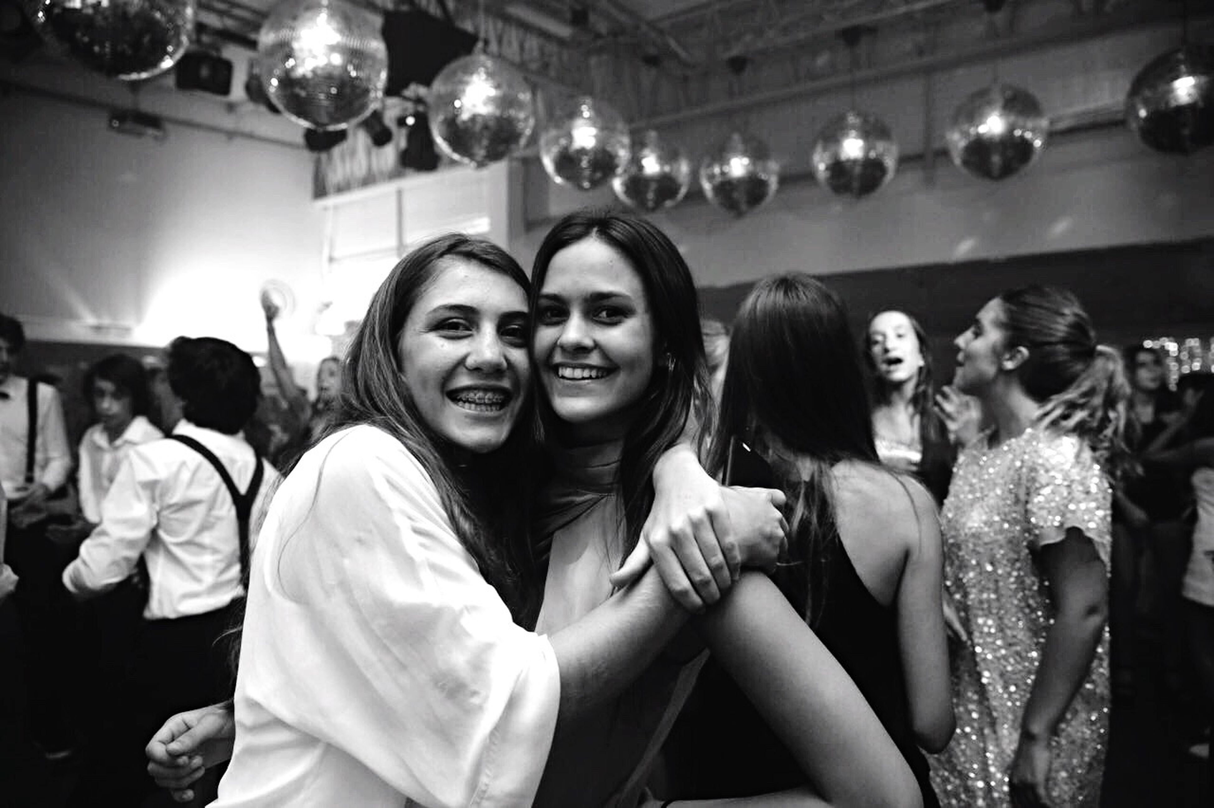 friendship, fun, leisure activity, real people, enjoyment, togetherness, smiling, happiness, lifestyles, night, indoors, nightlife, nightclub, portrait, young women, party - social event, young adult, glamour, looking at camera, cheerful, beautiful woman, bonding, people