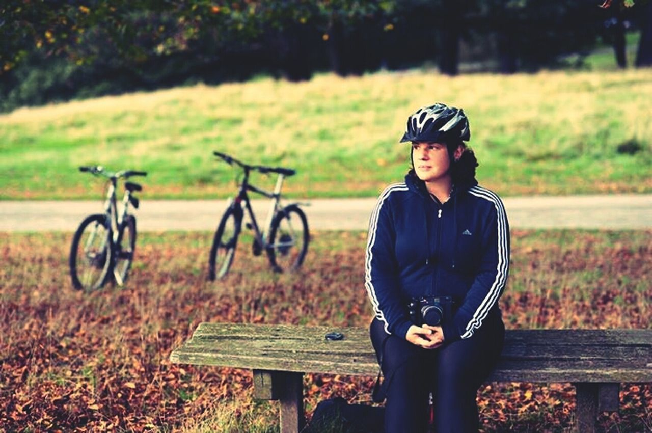 real people, field, one person, bicycle, lifestyles, leisure activity, outdoors, day, young adult, young women, nature, cycling helmet, headwear, tree, people