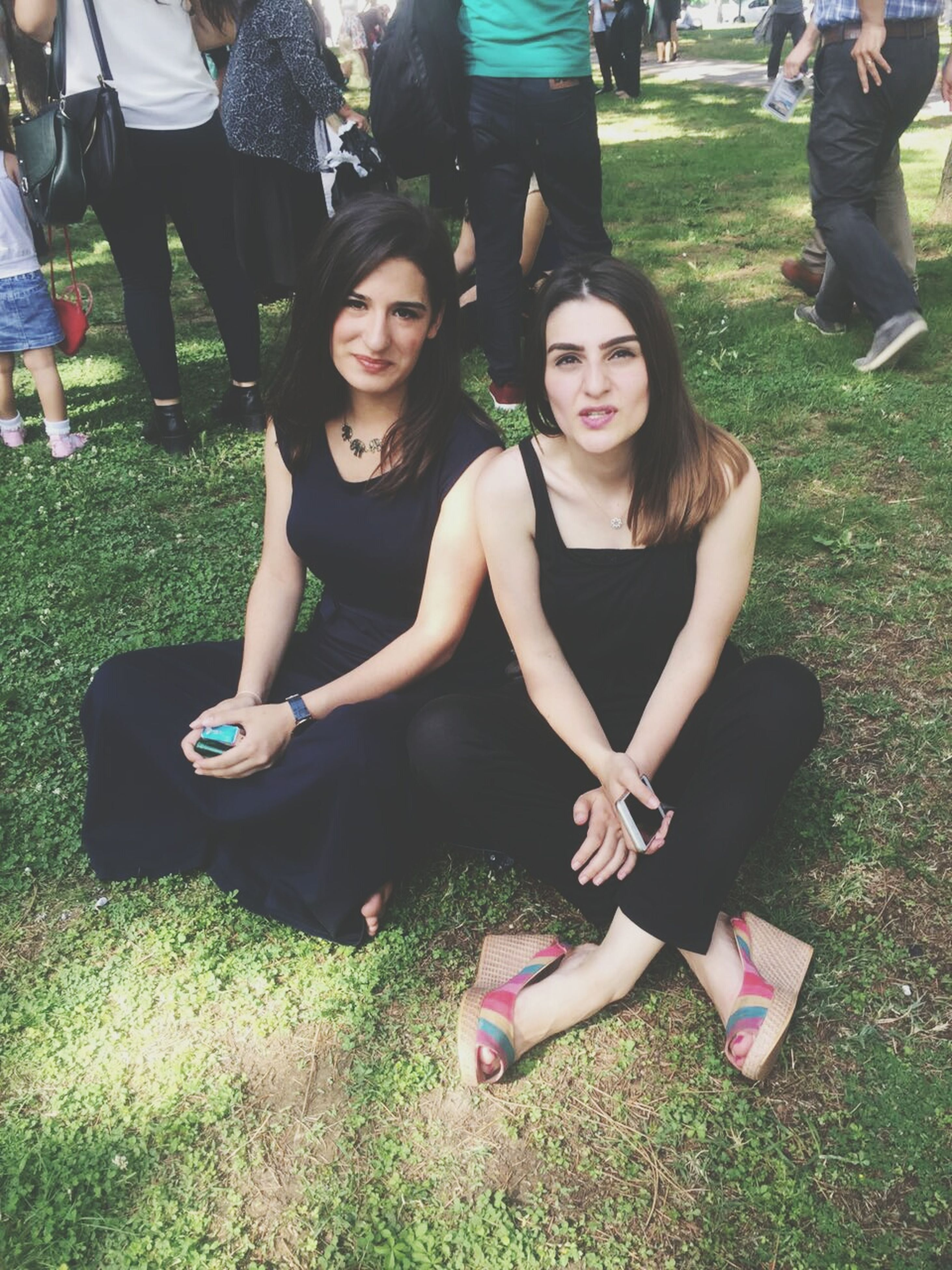 lifestyles, leisure activity, grass, casual clothing, sitting, togetherness, person, park - man made space, young adult, friendship, young women, enjoyment, smiling, fun, front view, happiness