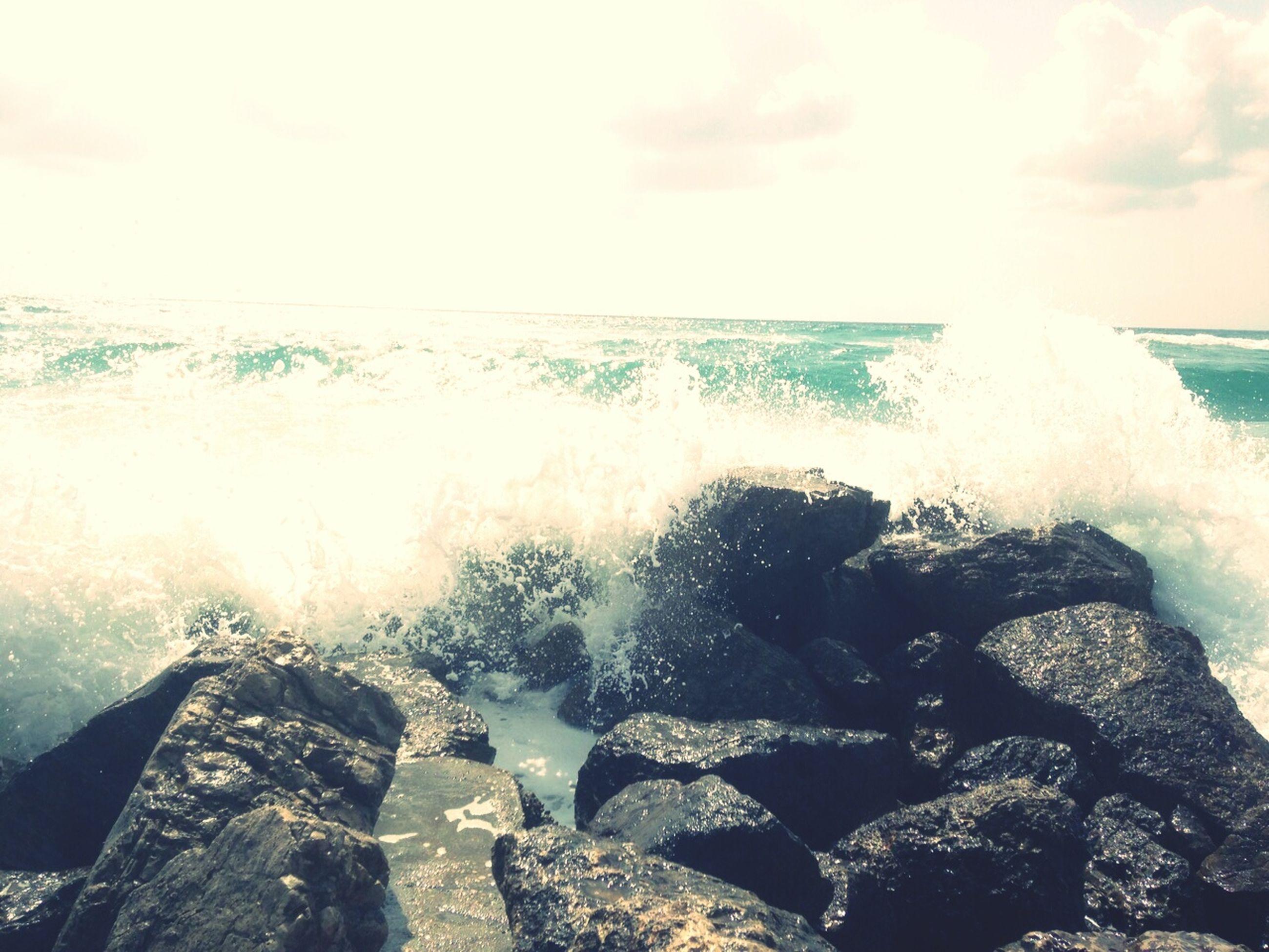 sea, water, horizon over water, rock - object, wave, sky, beauty in nature, scenics, beach, shore, nature, splashing, surf, motion, sunlight, sunbeam, sun, lifestyles, leisure activity