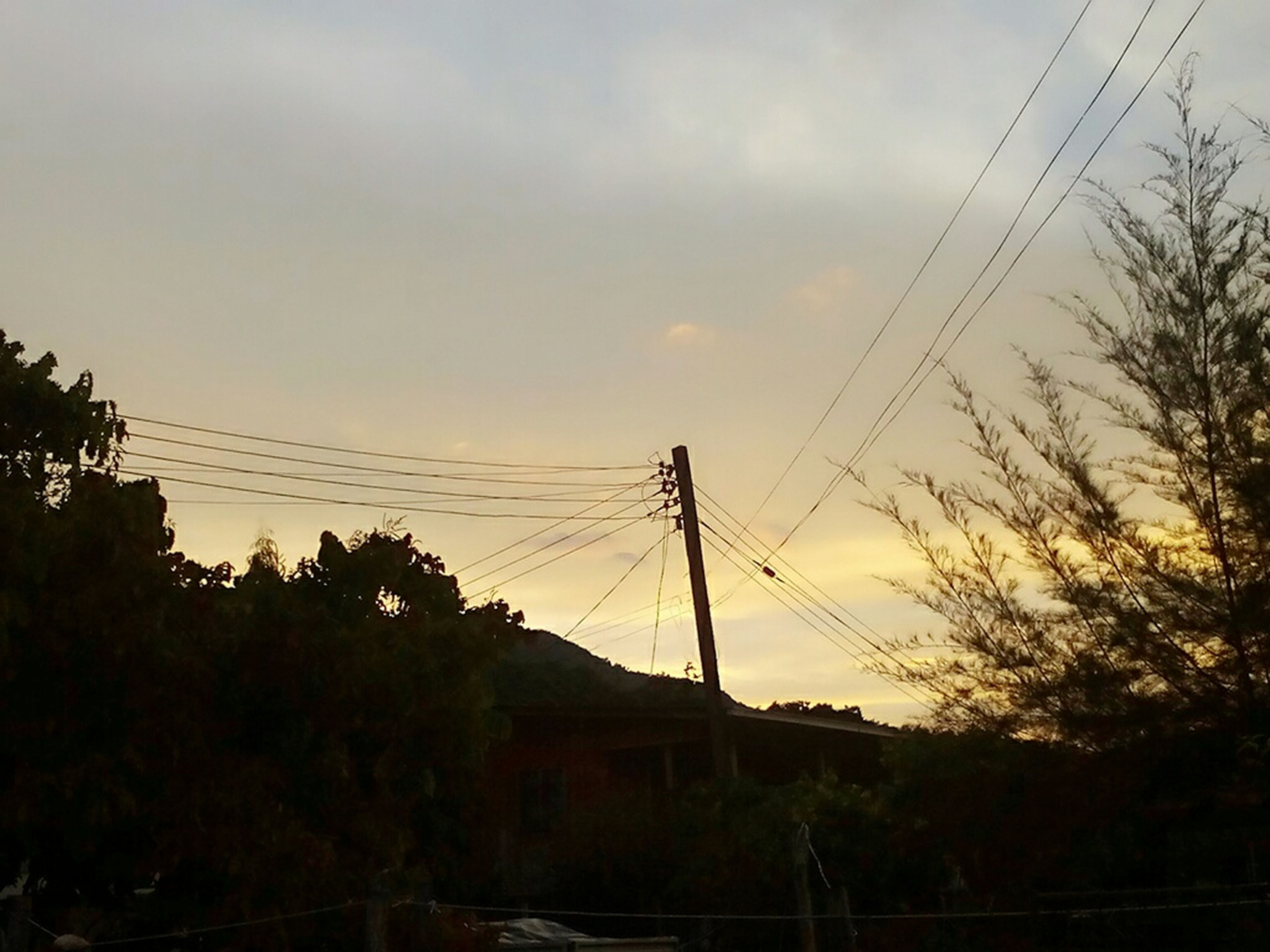 power line, electricity pylon, electricity, sky, power supply, cable, tree, silhouette, connection, sunset, low angle view, fuel and power generation, built structure, building exterior, cloud - sky, house, architecture, power cable, dusk, technology