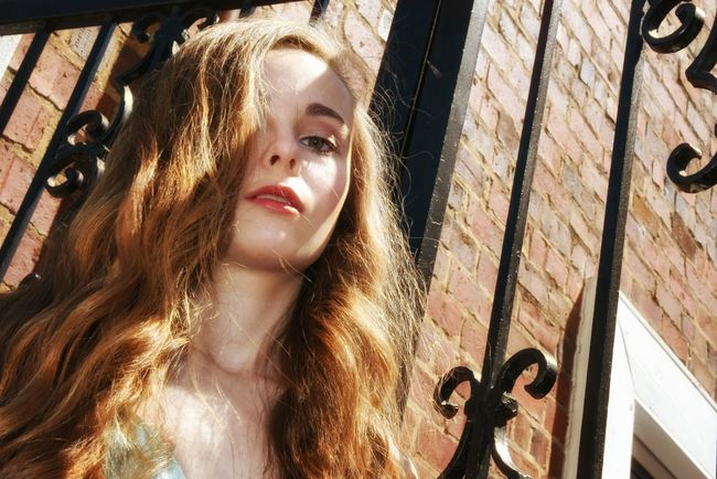 Girl at the gate - Pretty Girl Blonde Girl Shadowplay Iron Gate Evening Wear Long Hair Afternoon Light Film Noir Fashion Photography Color Portrait Outside Portrait Of A Girl Portrait Of A Woman Dreamy Portrait Outdoors Sunset Brick Wall Old Buildings