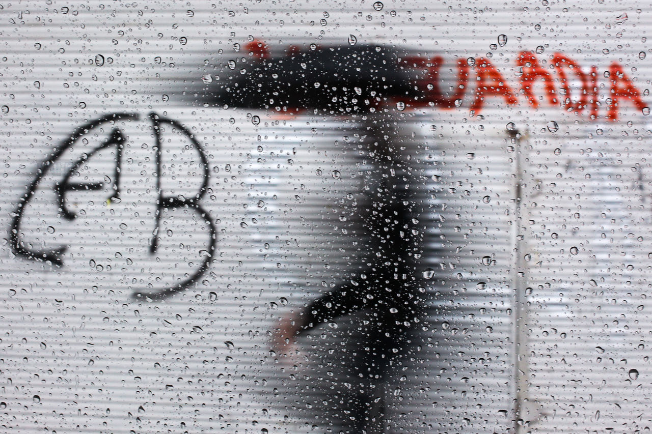 A PERSON WALKING IN THE RAIN AND THE PHOTOGRAPHER TAKING PHOTO from behind a window glass. Argentina Contrast Dark Detail Glass Glass - Material Graffitti Move Person Rain Shadow Symbol Transparent Umbrela Walk Woman