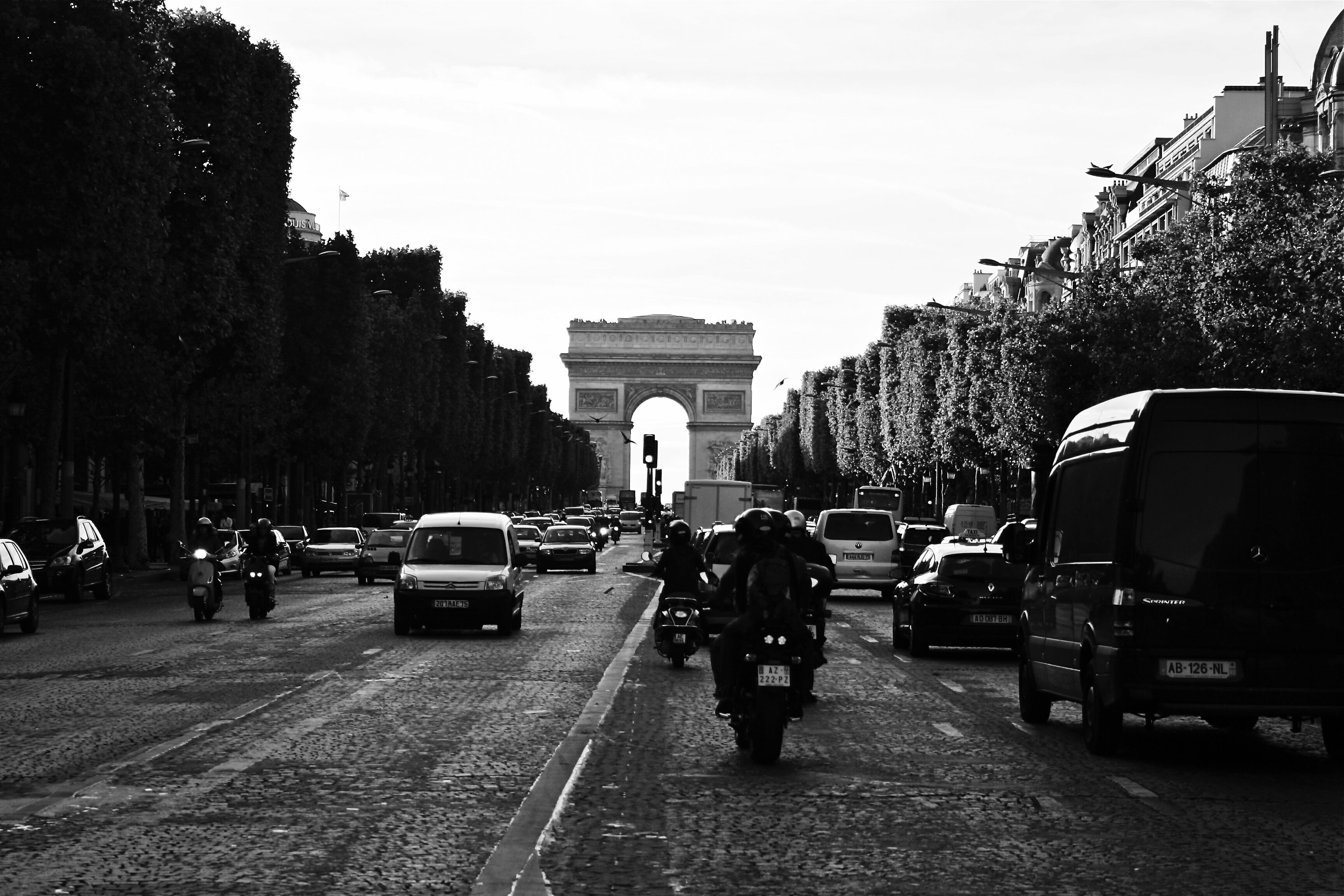 land vehicle, transportation, car, architecture, mode of transport, built structure, travel, street, arch, sky, real people, road, walking, the way forward, outdoors, travel destinations, large group of people, building exterior, triumphal arch, men, day, city, people