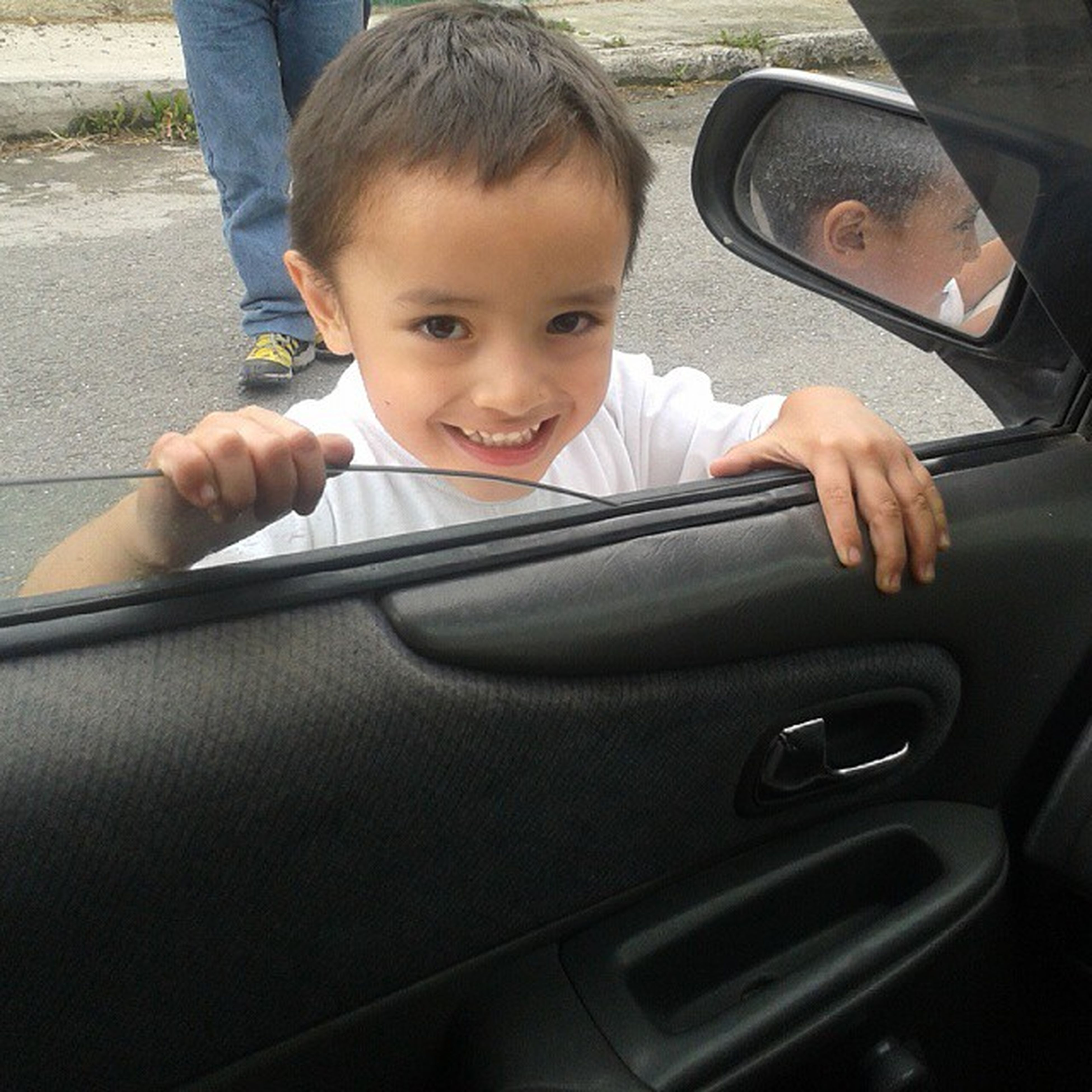 transportation, childhood, indoors, mode of transport, sitting, land vehicle, lifestyles, car, elementary age, boys, holding, leisure activity, innocence, person, casual clothing, cute, vehicle interior, front view