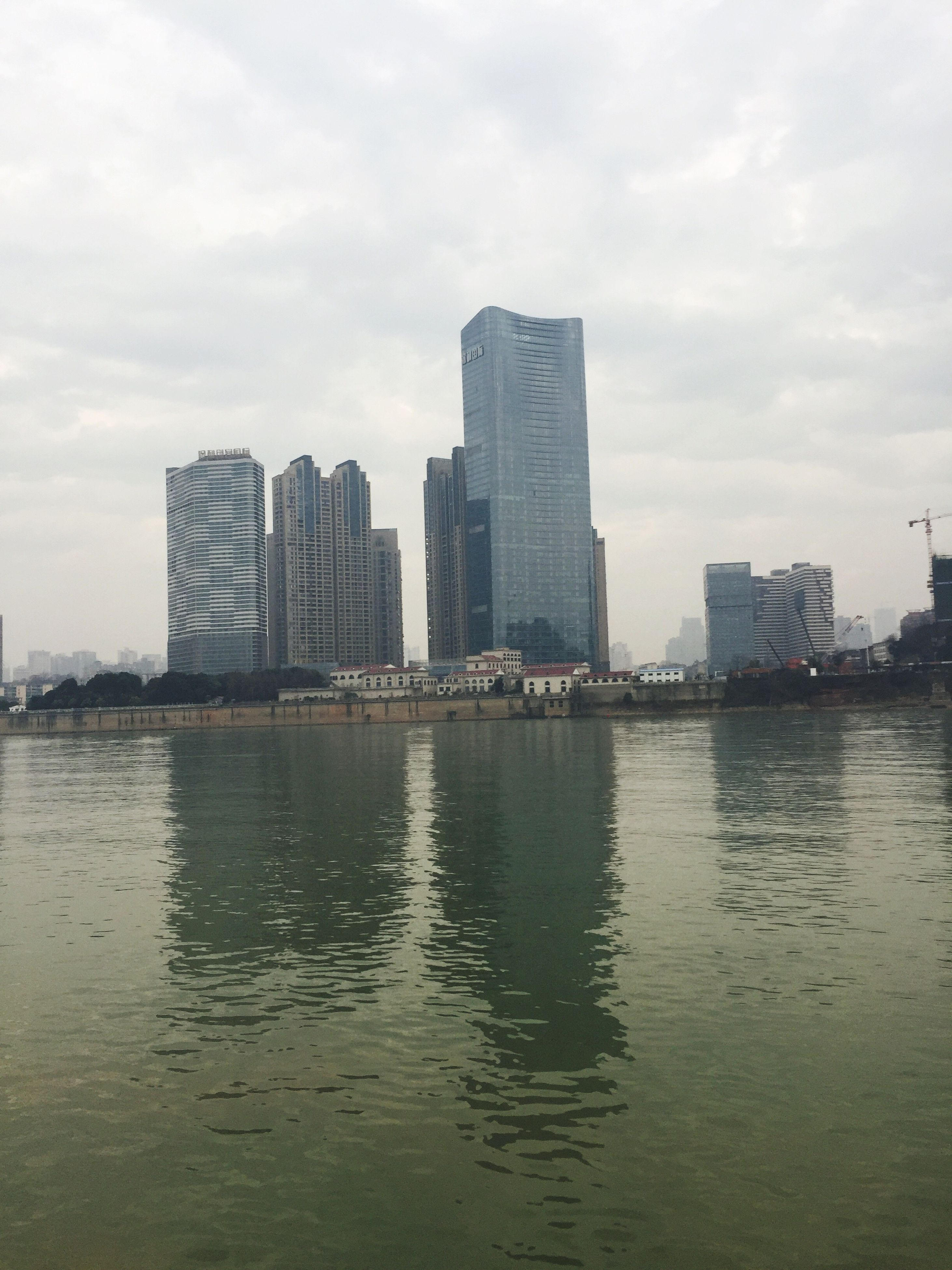 city, building exterior, architecture, skyscraper, built structure, water, urban skyline, sky, cityscape, cloud - sky, modern, outdoors, building, day, no people, residential building, nature, downtown district
