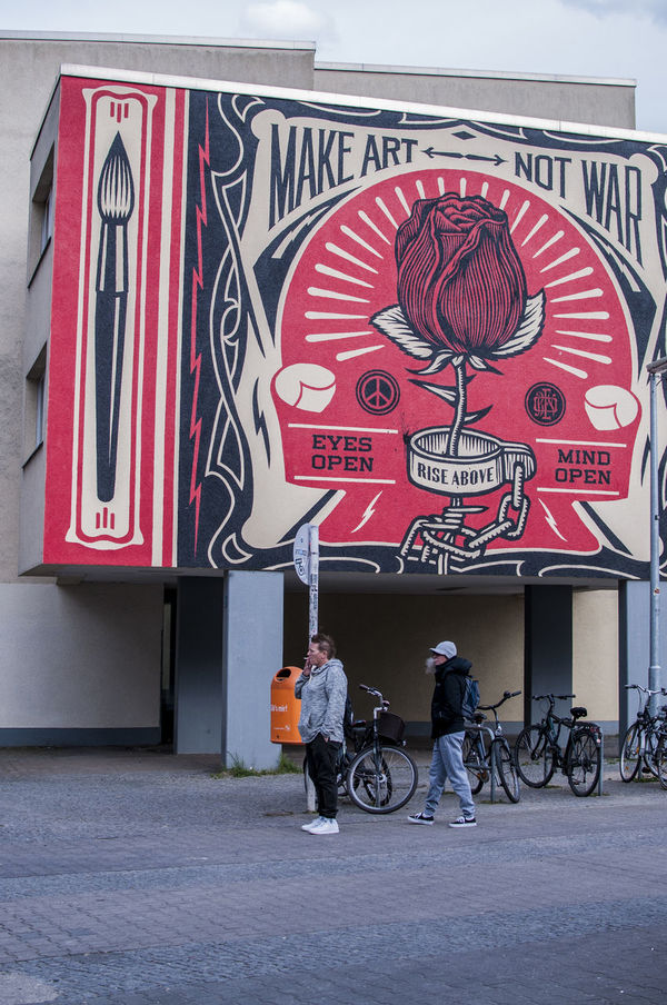Make Art Not War Architecture Berlin Bicycle Building Building Exterior Built Structure City Day EyeEmNewHere Make Art Make Art Not War Men Outdoors People Real People Rose - Flower Standing Street Streetphotography Text The Street Photographer - 2017 EyeEm Awards