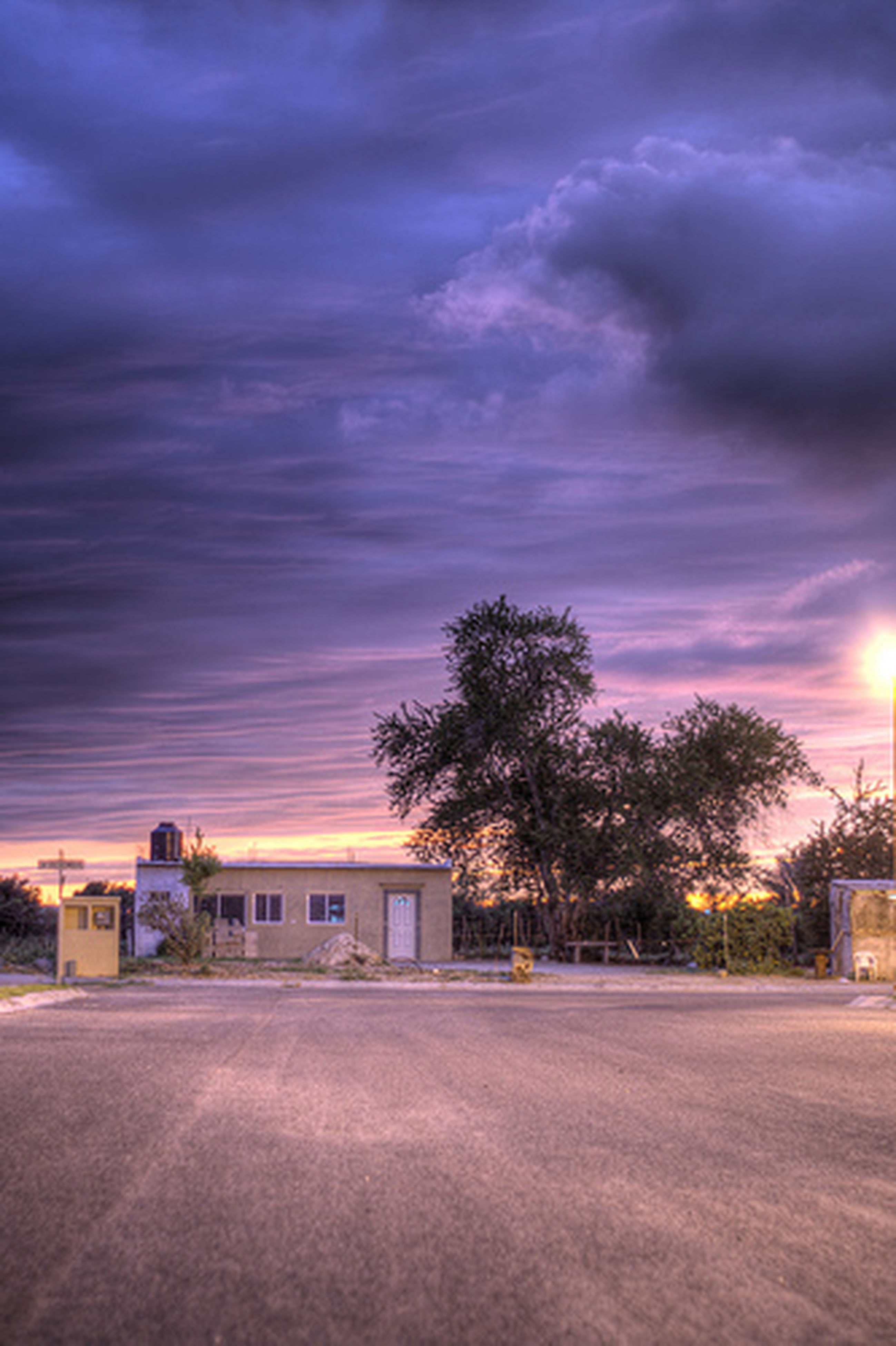 sky, cloud - sky, tree, building exterior, sunset, architecture, cloudy, built structure, road, the way forward, weather, house, street, dusk, transportation, cloud, nature, tranquility, empty, outdoors