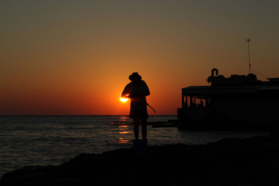 while the sun sets a man, peacfully, pre 2015  Beauty In Nature Fisherman Horizon Over Water Italy Nature Outdoors Puglia Sea Silhouette Sun Sunset Water