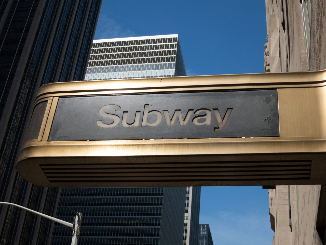 New York City Subway entrance, gold sign. Skyscrapers and blue sky in the background. Architecture Building Exterior Built Structure Day Daytime Façade Gold Midtown Manhattan New York City No People NYC NYC Photography Outdoors Sign Skyscraper Skyscrapers In The Clouds Subway Subway Station Subway Station Sign Travel Travel Destinations