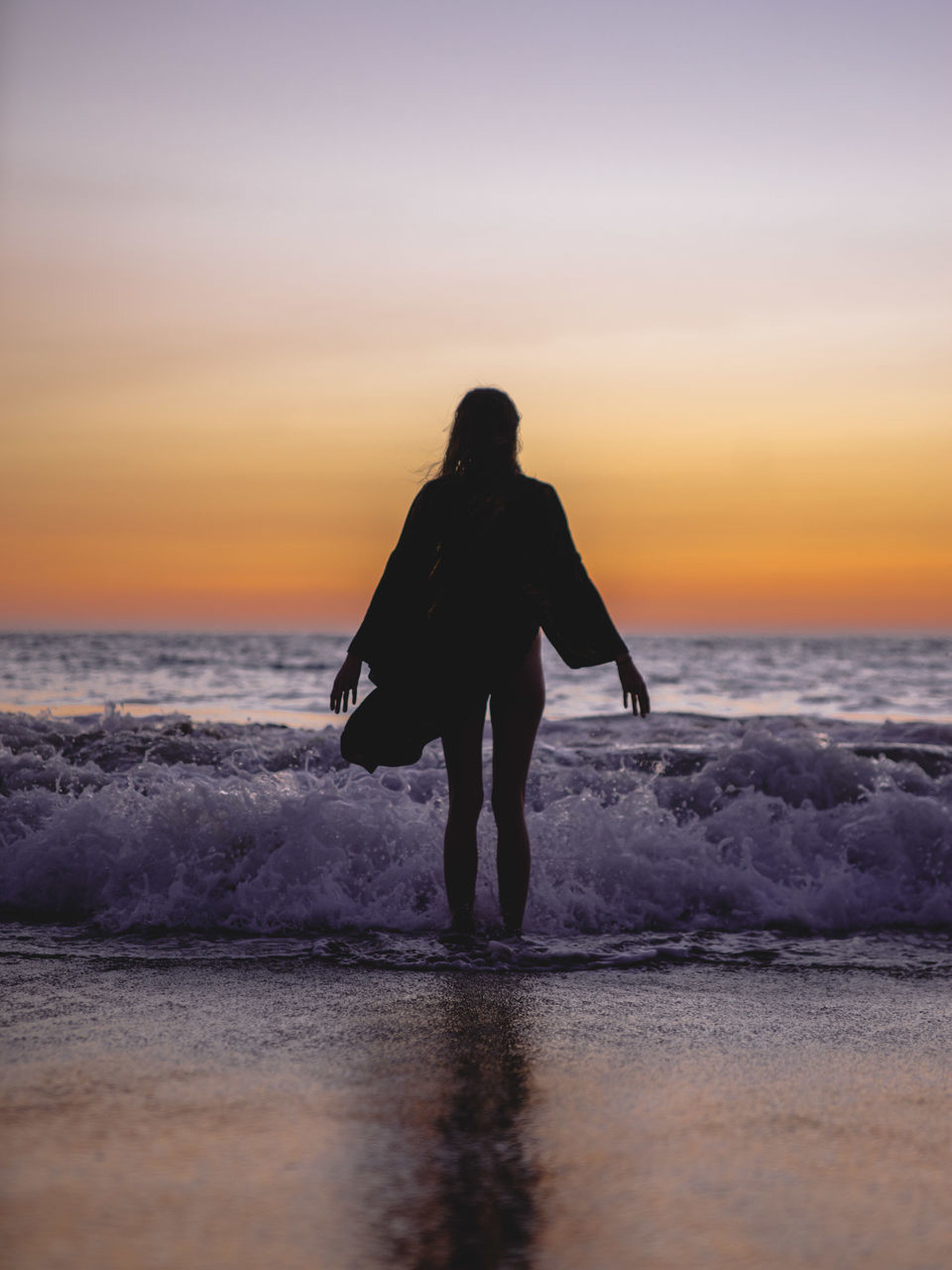 sea, sunset, water, beach, horizon over water, beauty in nature, silhouette, nature, sky, scenics, one person, real people, leisure activity, full length, wave, tranquility, lifestyles, tranquil scene, outdoors, walking, rear view, women, vacations, standing, men, ankle deep in water, day, people