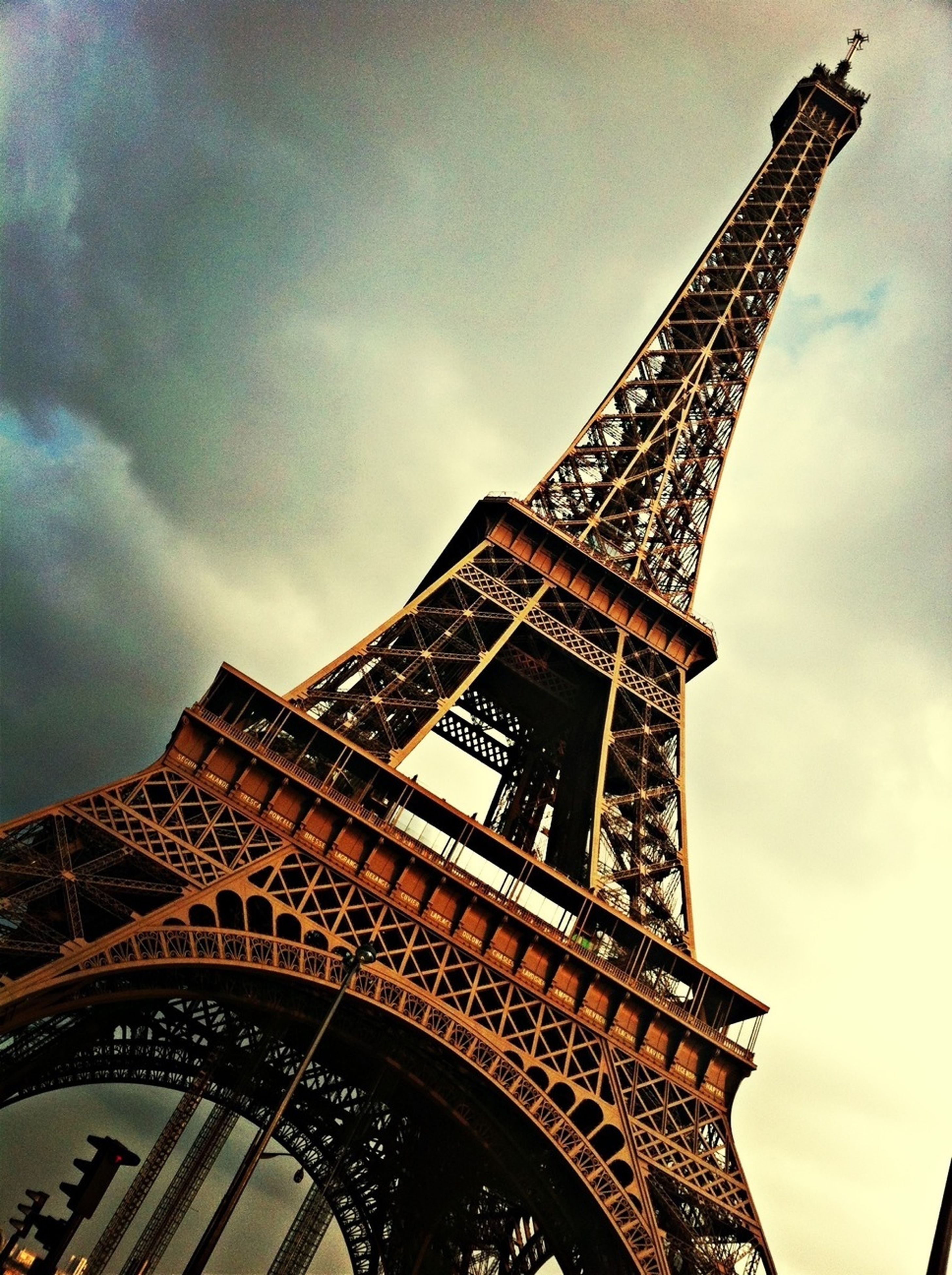 architecture, built structure, international landmark, famous place, low angle view, travel destinations, tourism, eiffel tower, capital cities, travel, sky, tower, history, culture, tall - high, building exterior, cloud - sky, architectural feature, city, cloudy