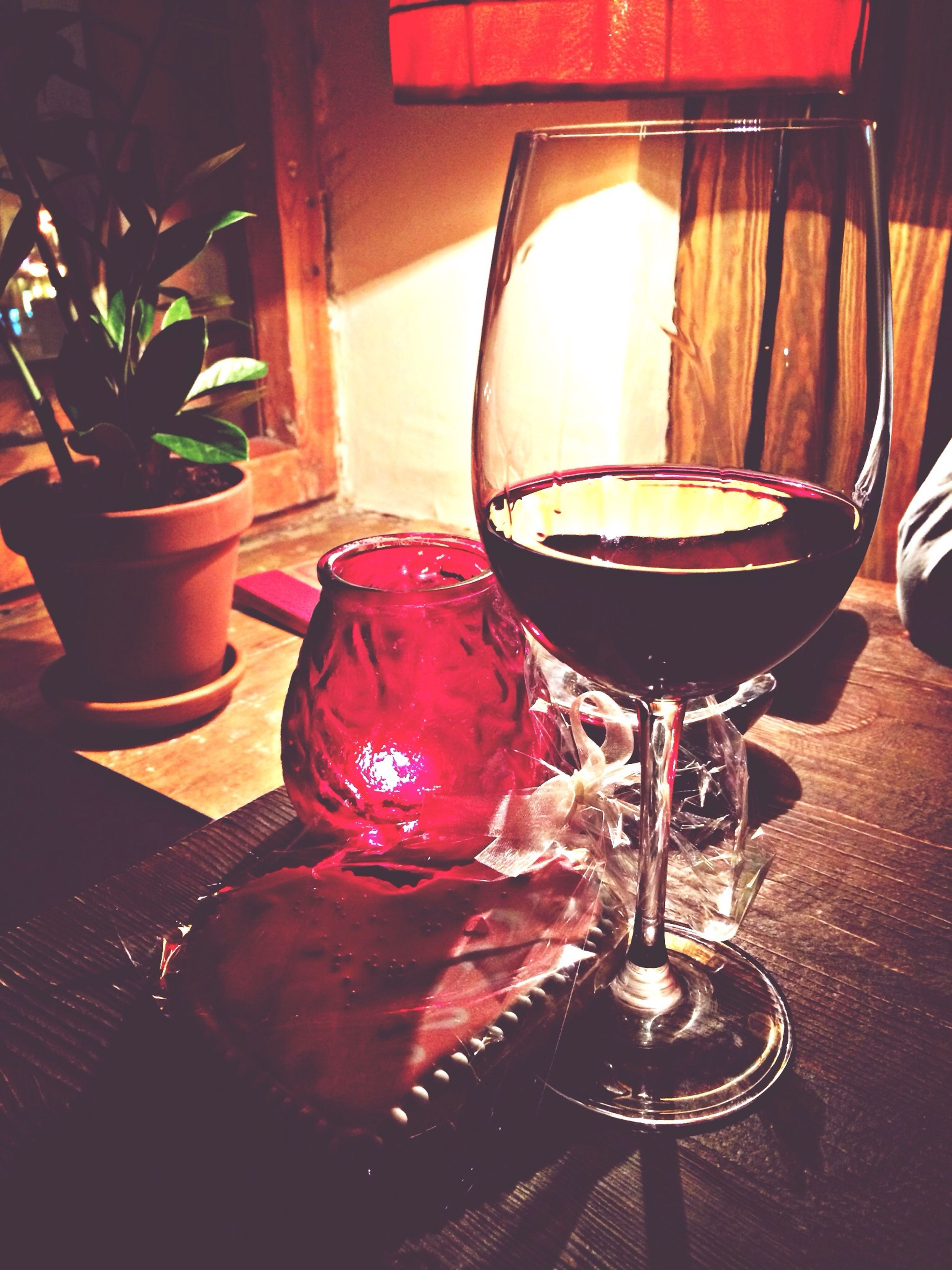 indoors, table, still life, wineglass, drink, home interior, glass - material, chair, vase, drinking glass, illuminated, close-up, food and drink, wine, restaurant, absence, no people, potted plant, place setting, red