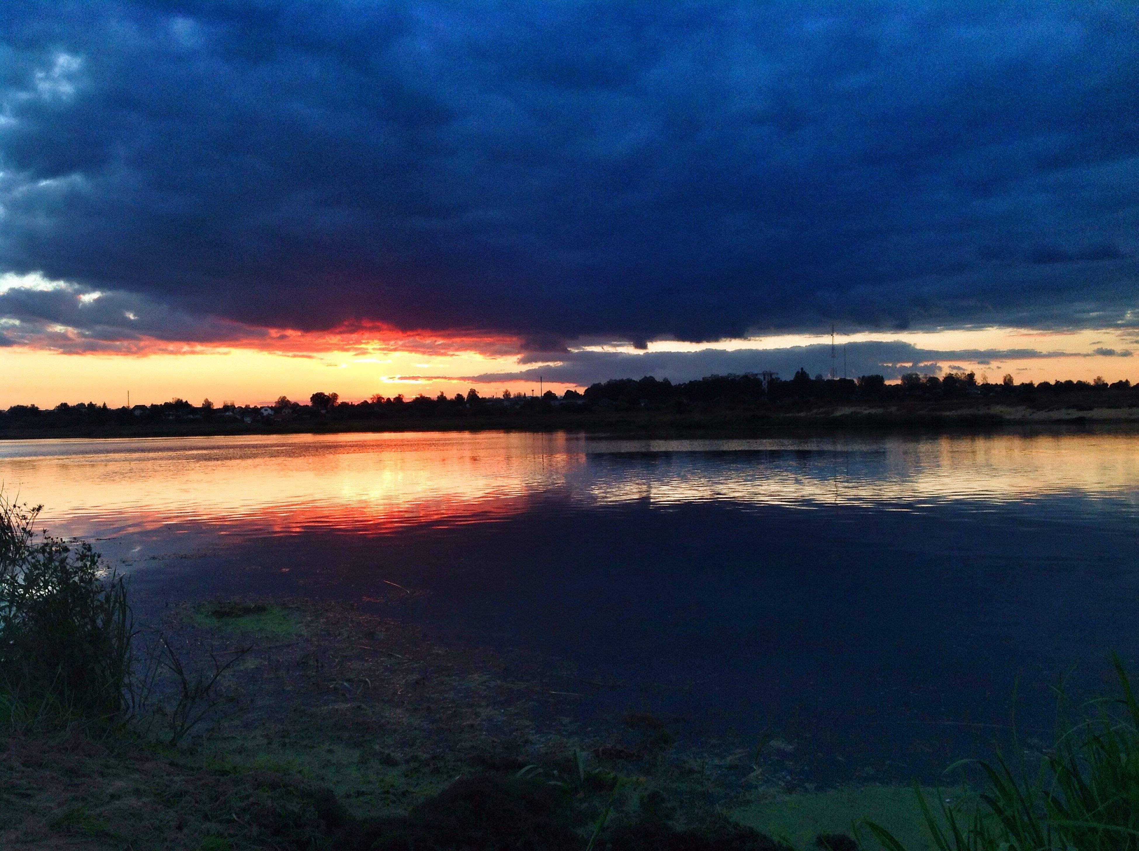water, tranquil scene, sunset, scenics, tranquility, lake, sky, beauty in nature, calm, blue, reflection, idyllic, cloud, nature, orange color, cloud - sky, atmospheric mood, non-urban scene, dramatic sky, moody sky, storm cloud, outdoors, cloudy, countryside, remote, sea, cloudscape, majestic, atmosphere
