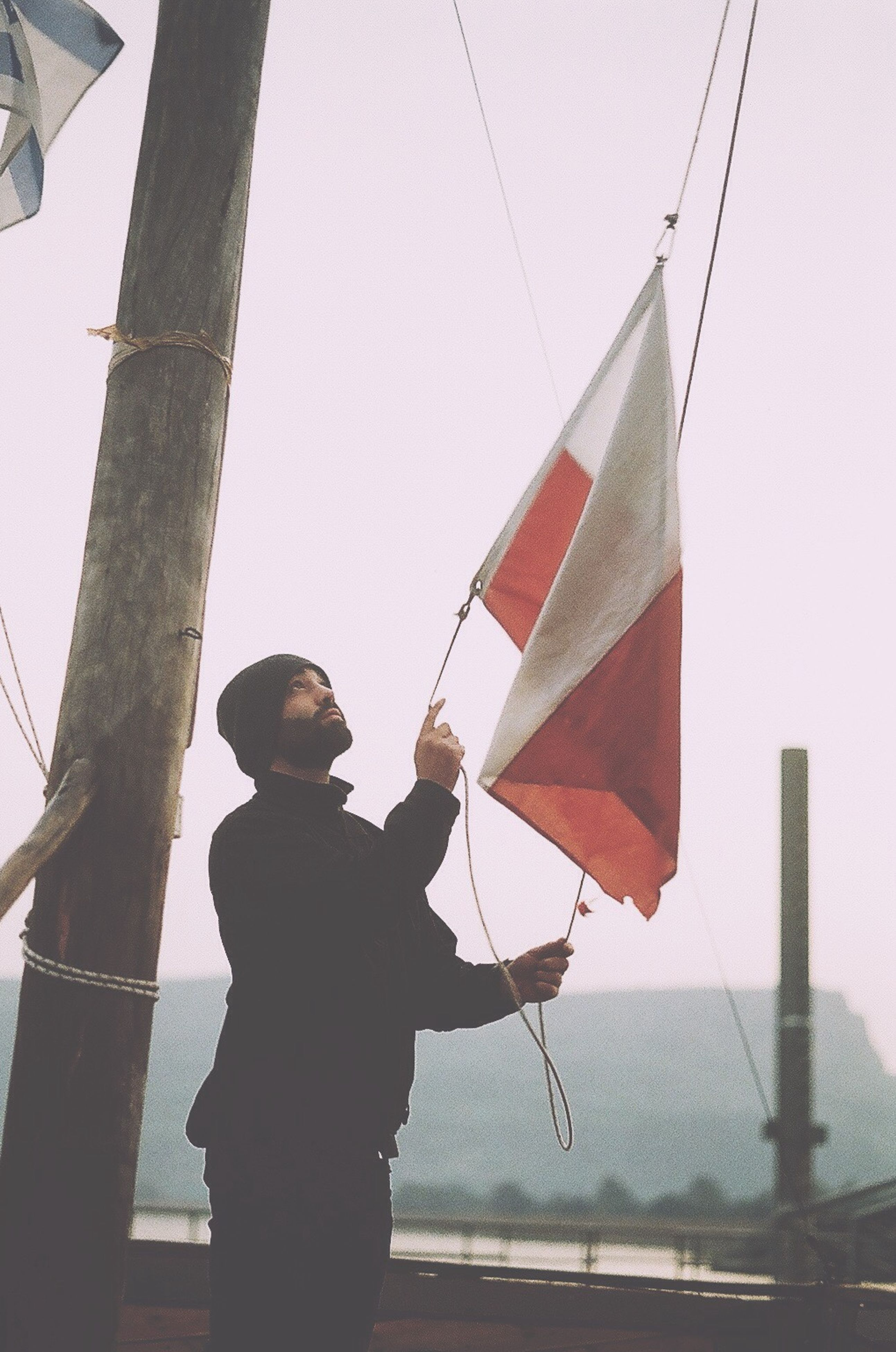 holding, one person, flag, one man only, adults only, standing, day, patriotism, people, real people, outdoors, adult, only men, men, sky