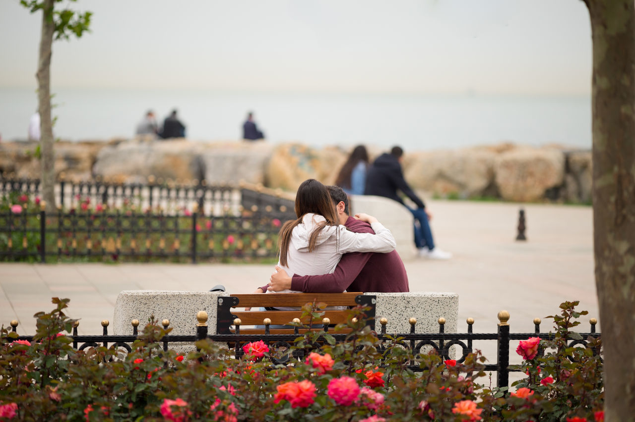 Couple Embracing On Bench At Park