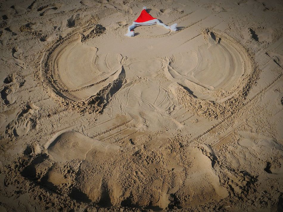 Christmas Around The World Snowangel Schneeengel im Sand am Strand Weihnachtsmütze Weihnachten Merry Christmas Christmastime
