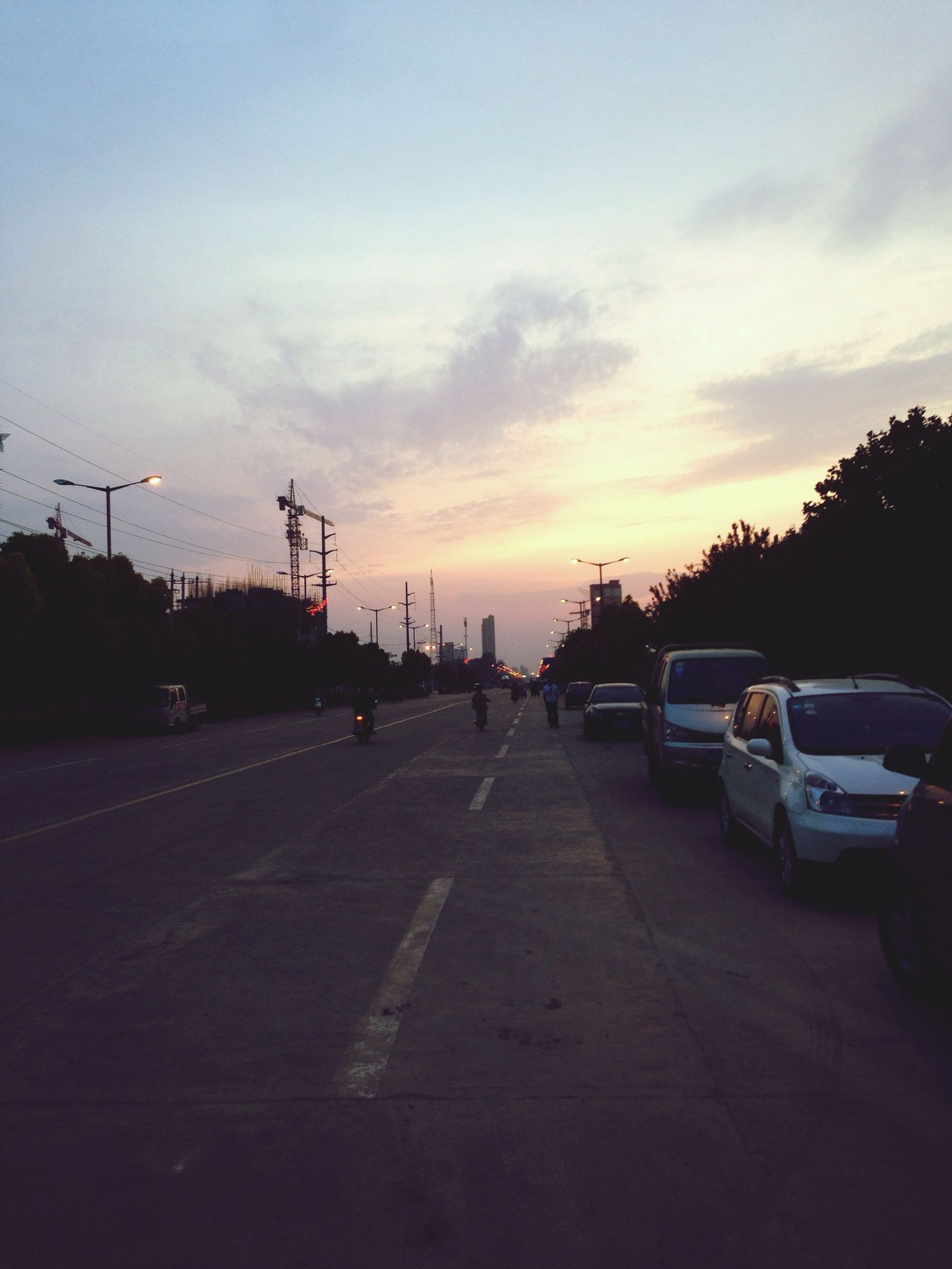 transportation, car, road, sunset, land vehicle, mode of transport, sky, the way forward, street, road marking, cloud - sky, silhouette, street light, diminishing perspective, cloud, vanishing point, on the move, outdoors, cloudy, no people