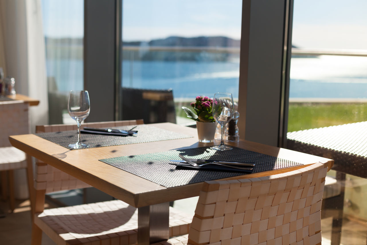 restaurant table by the window Arranged Chair Clean Day Decoration Dining Table Elegant Empty Event Exclusive  Flower Flowerpot Formal Glass Indoors  Luxury Mat No People Place Setting Restaurant Sea View Sliding Door Table Window Wineglass