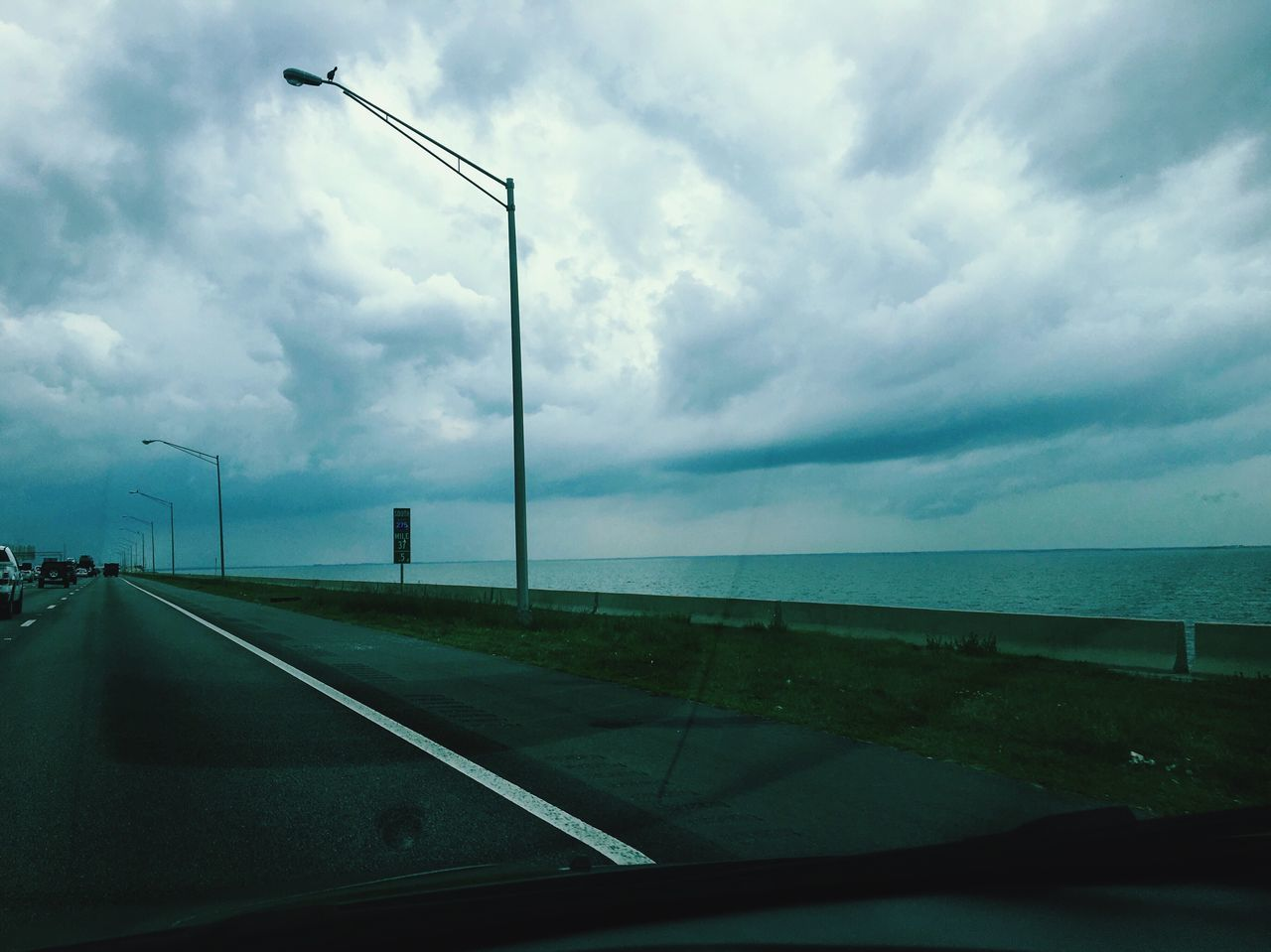 transportation, cloud - sky, sky, car, mode of transport, road, windshield, day, no people, water, sea, street light, car interior, nature, scenics, the way forward, outdoors, beauty in nature, horizon over water