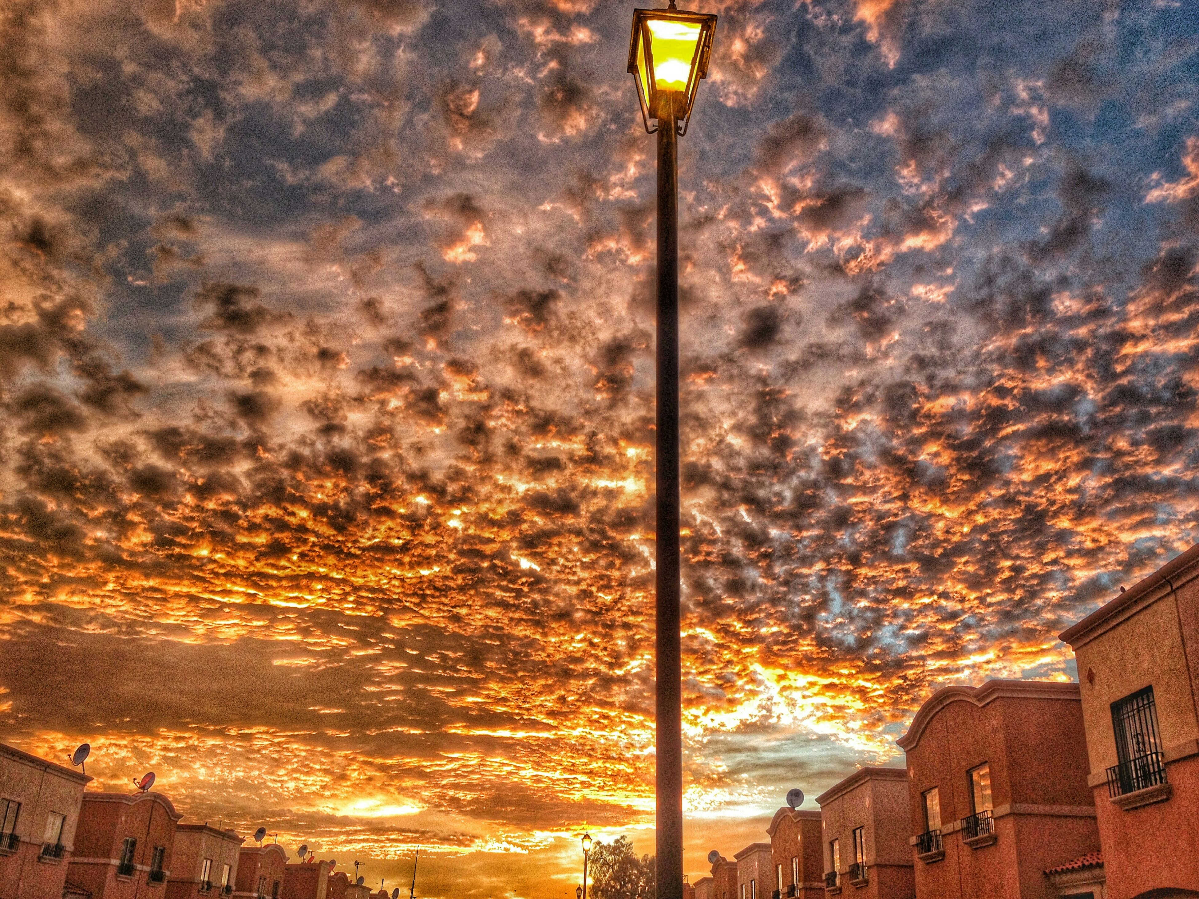 street light, architecture, built structure, lighting equipment, sky, residential building, city, power line, residential structure, building, outdoors, illuminated, cloud - sky, no people, cable, town, residential district, pole, city life, nature, weather, cloud