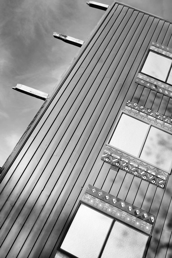 The building is slanted Angle Architecture Blackandwhite Building Cloud - Sky Cropped Lines Low Angle View Modern No People Outdoors Pattern Shadow Sky Slanted Textures And Surfaces Windows