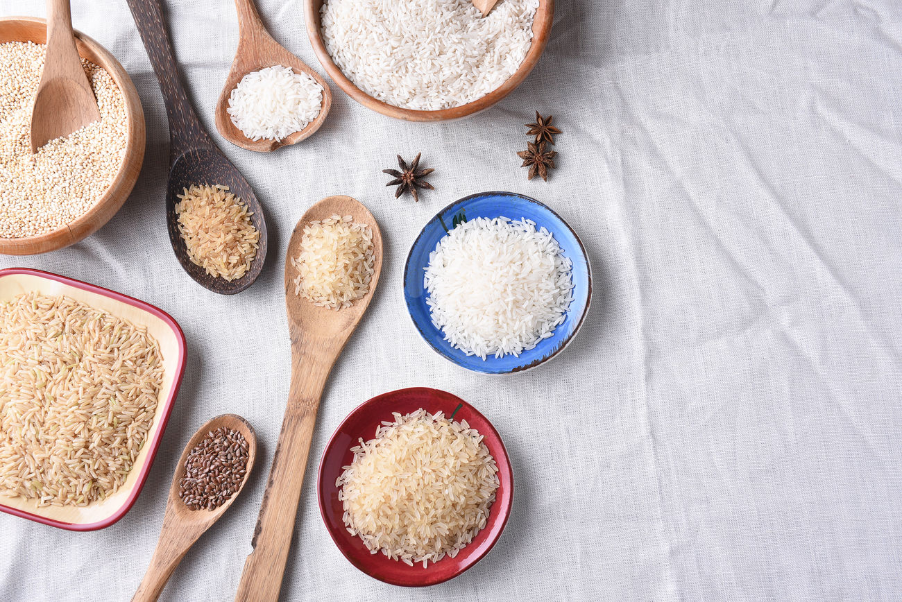 High angle view of a group of bowls and spoons filled with various varieties of rice and grains. Bowls Brown Rice Flax Flax Seeds Food Grain High Angle View Oats Quinoa Rice Seed Star Anise Still Life Utensil White Rice Wooden Spoon