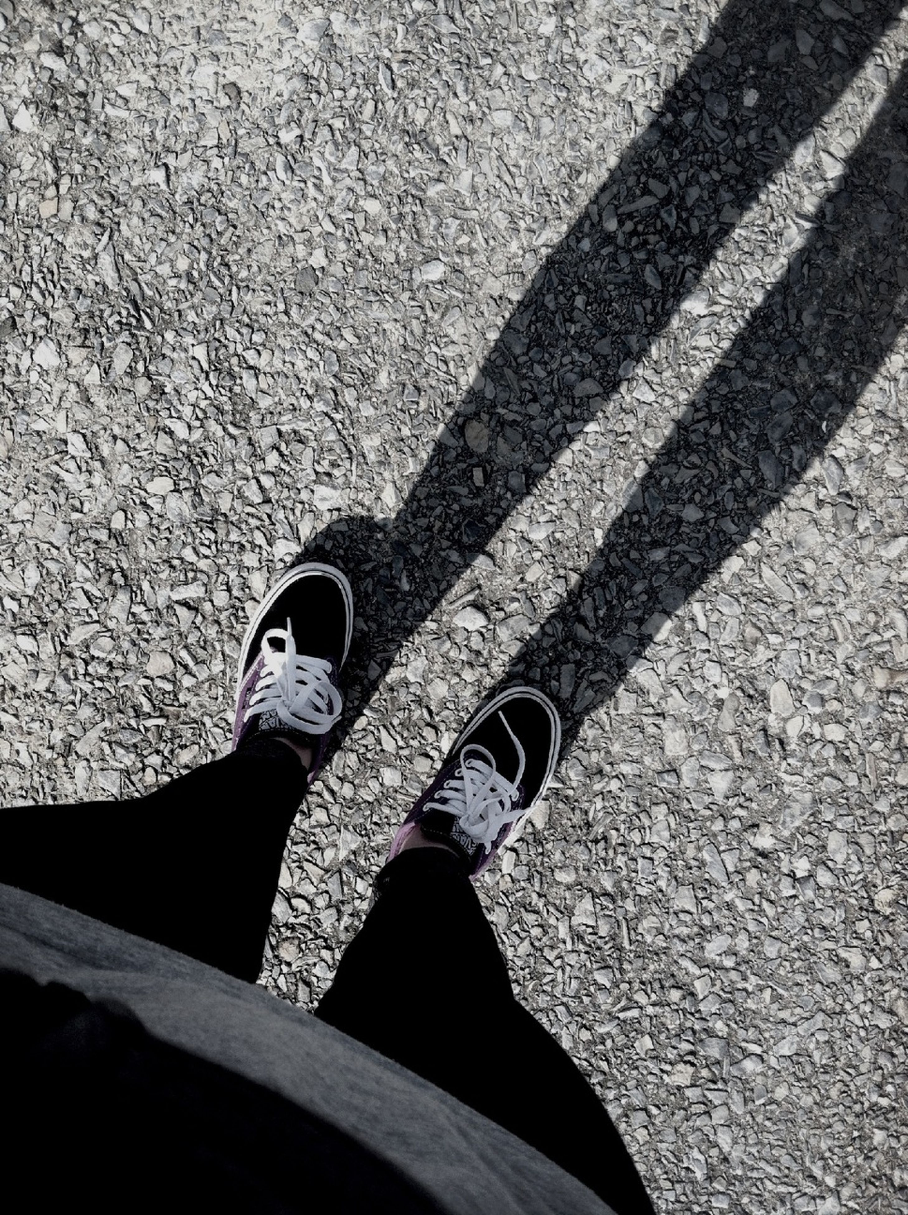 low section, shoe, person, high angle view, standing, jeans, personal perspective, lifestyles, footwear, street, day, leisure activity, asphalt, road, human foot, outdoors, sunlight