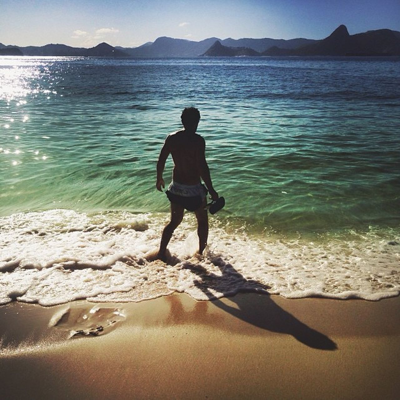 sea, real people, beach, water, lifestyles, nature, sand, leisure activity, full length, one person, beauty in nature, scenics, shadow, sunlight, vacations, outdoors, day, men, mountain, sky, young adult, people
