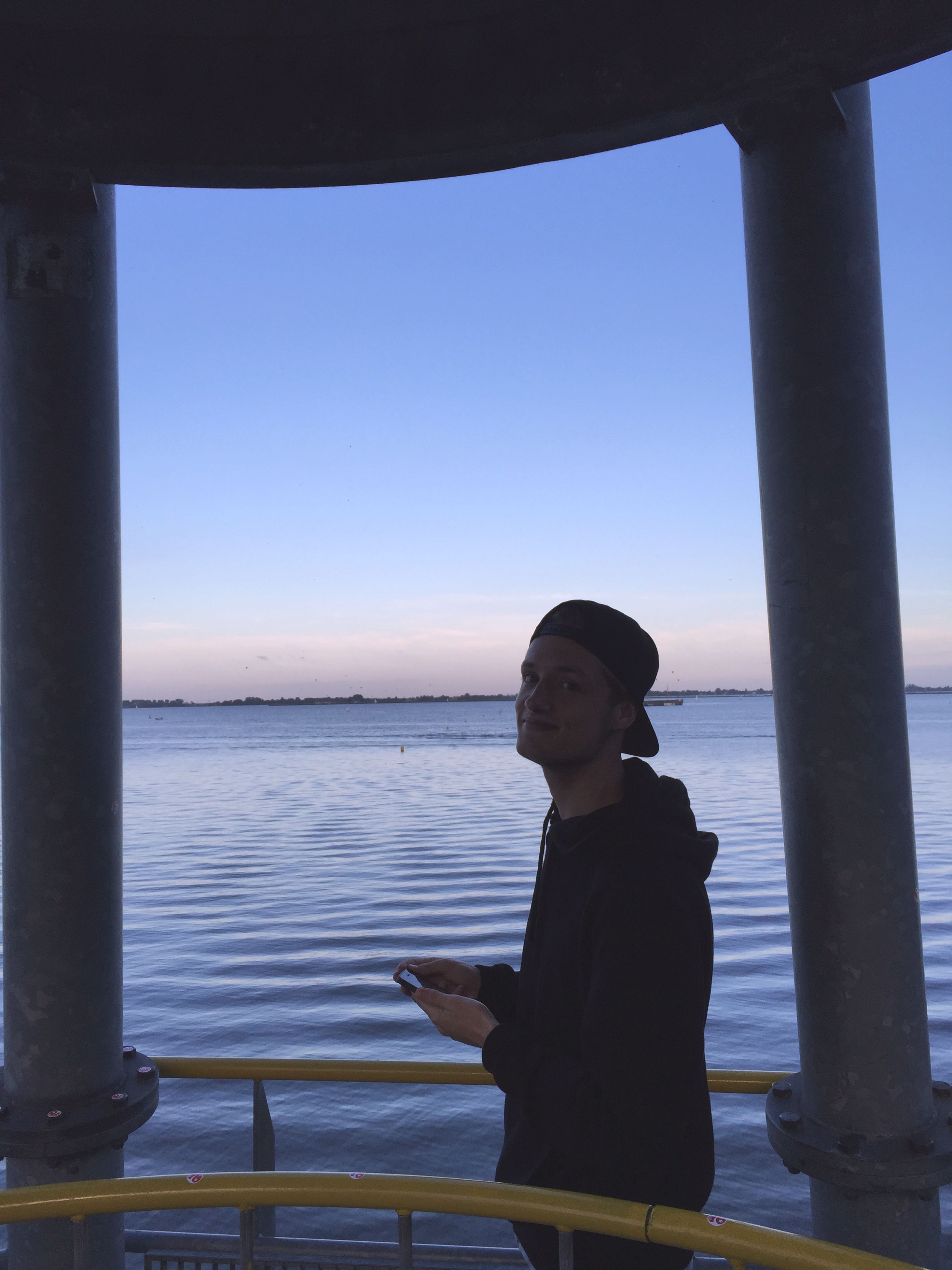 clear sky, water, sea, horizon over water, copy space, tranquility, silhouette, scenics, tranquil scene, indoors, nature, beauty in nature, railing, sky, architectural column, sunlight, day, built structure, sunset