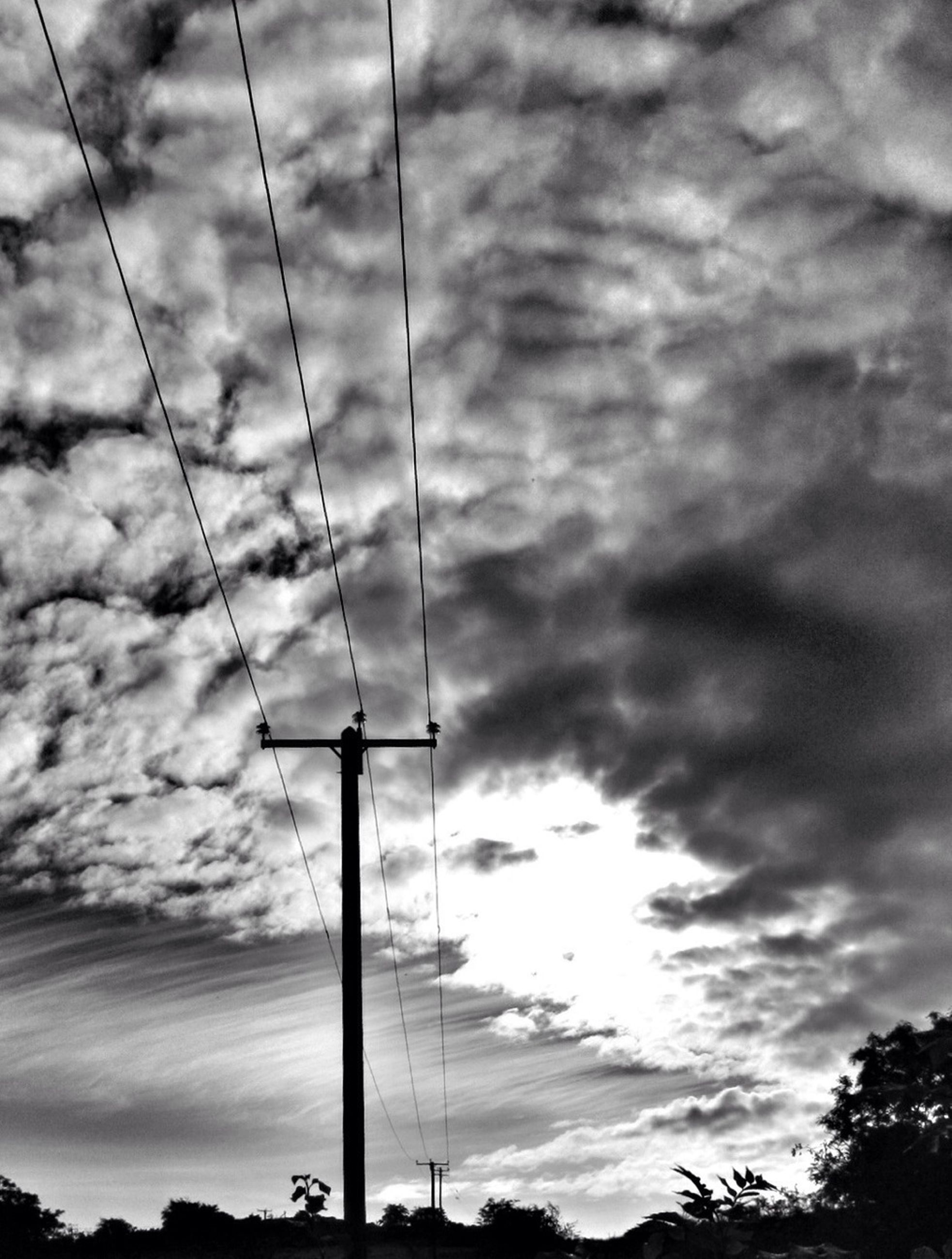 sky, low angle view, cloud - sky, cloudy, silhouette, sunset, cloud, street light, fuel and power generation, electricity pylon, power line, electricity, technology, overcast, weather, tree, pole, nature, power supply, no people
