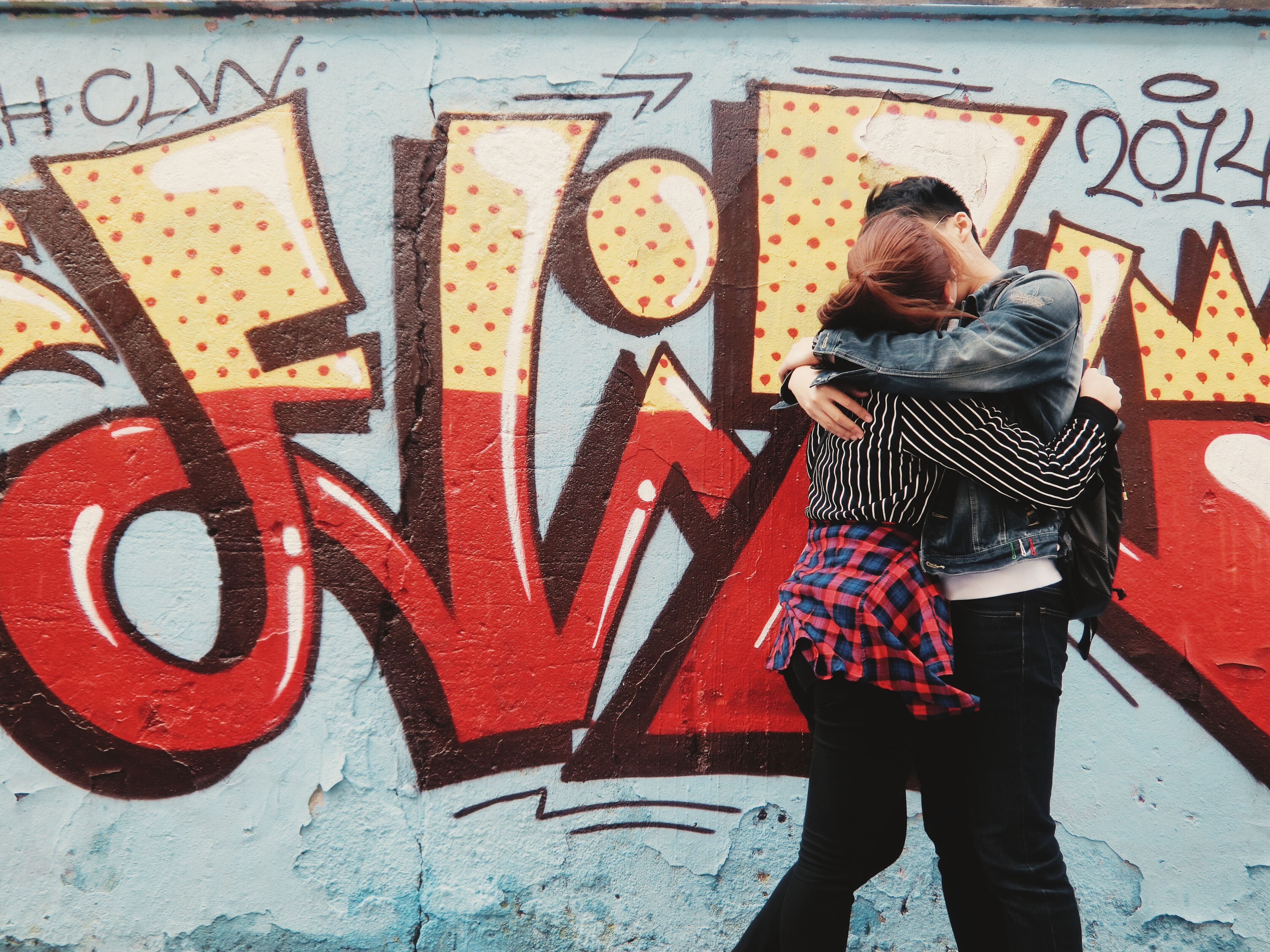lifestyles, standing, casual clothing, leisure activity, text, communication, full length, wall - building feature, men, red, sidewalk, three quarter length, graffiti, person, rear view, street, outdoors