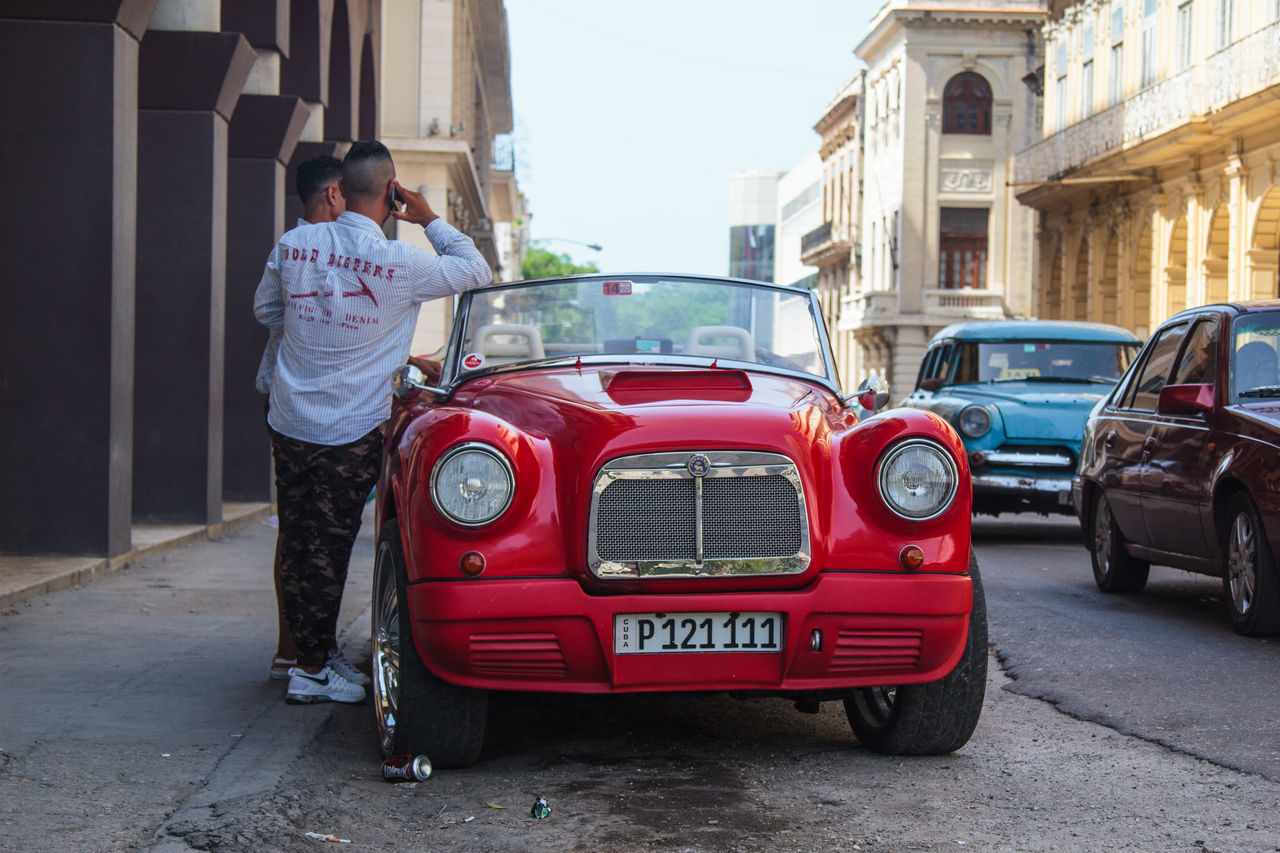 car, building exterior, transportation, full length, architecture, built structure, vintage car, day, standing, casual clothing, red, one person, outdoors, mode of transport, men, real people, collector's car, land vehicle, one man only, only men, young adult, adult, adults only, people