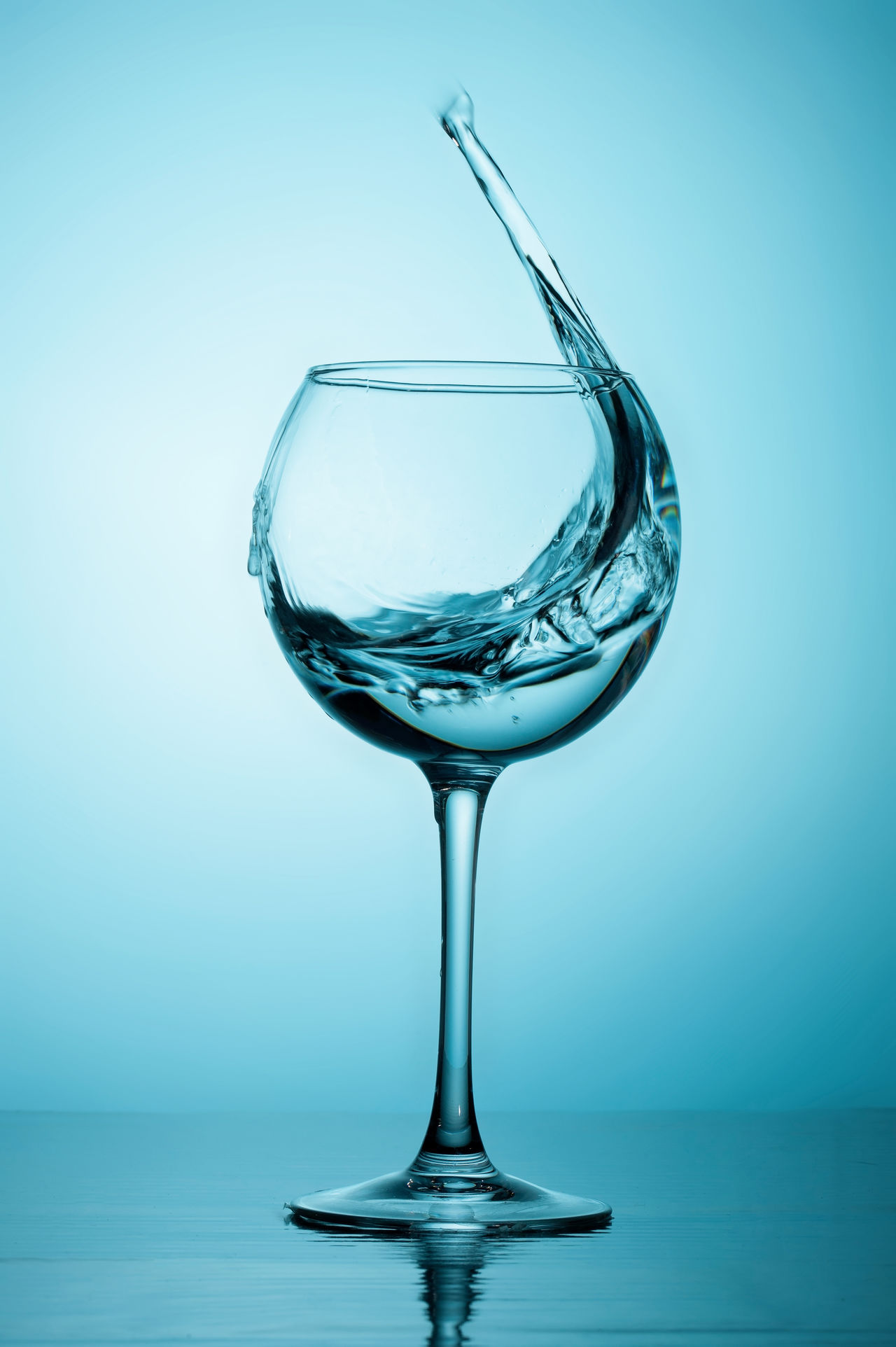 Water splash Alcohol Blue Blue Sky Clear Blue Sky Clear Water Day Drink Drinking Glass Fragility Freshness Motion No People Reflection Science Splashing Studio Shot Water Wineglass