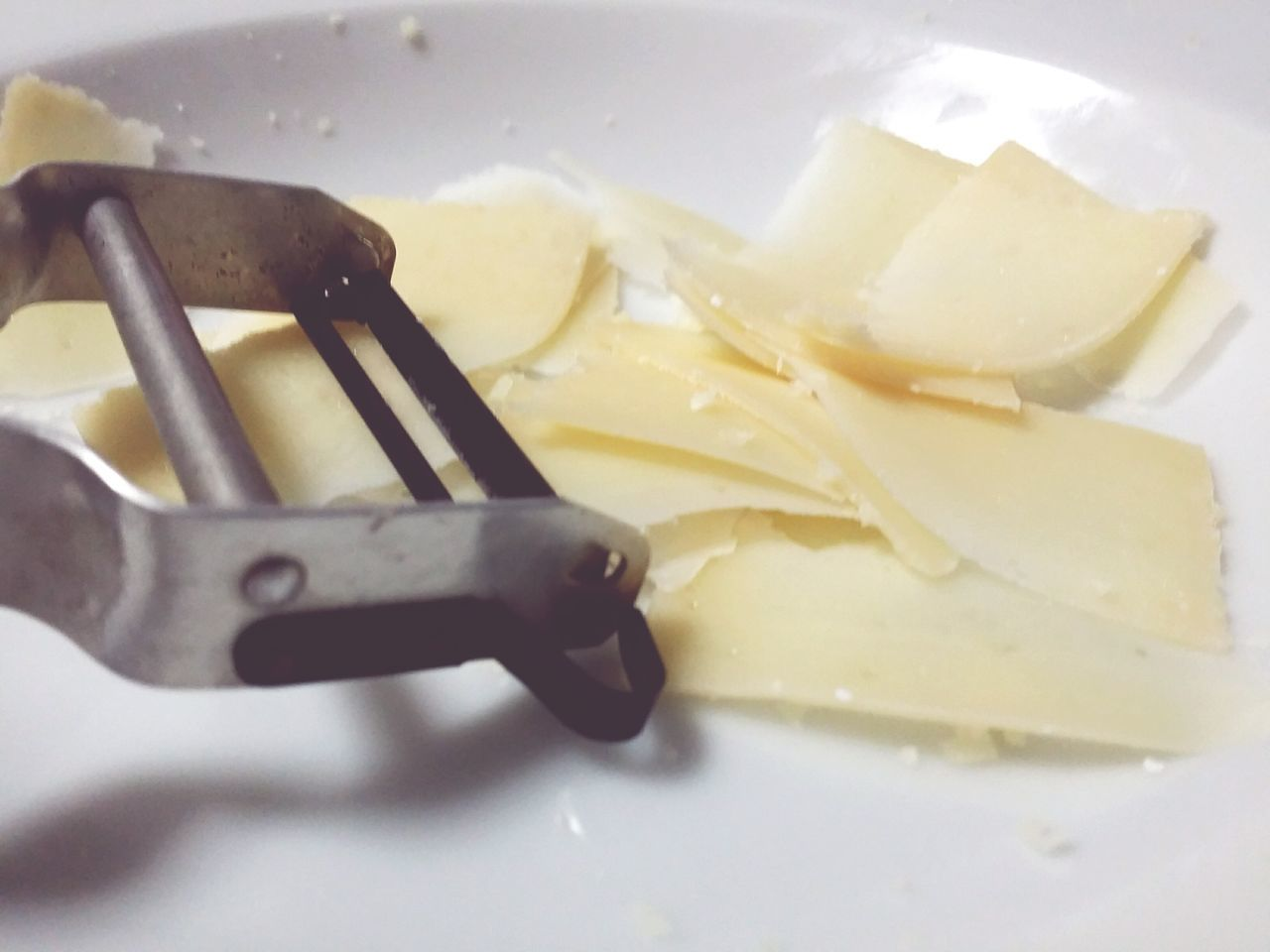 Peeler And Cheese Slices On Plate