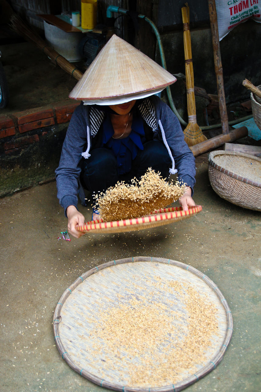 real people, food, occupation, asian style conical hat, one person, men, market, women, outdoors, day, freshness, adult, people