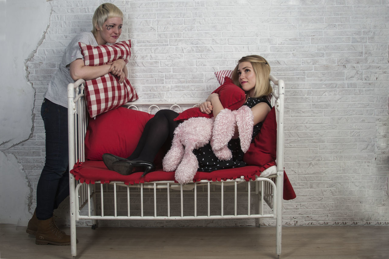 full length, sitting, indoors, looking at camera, chair, togetherness, two people, smiling, portrait, happiness, casual clothing, sofa, leisure activity, home interior, girls, bonding, childhood, blond hair, domestic life, living room, day, young women, real people, young adult, friendship, adult, people