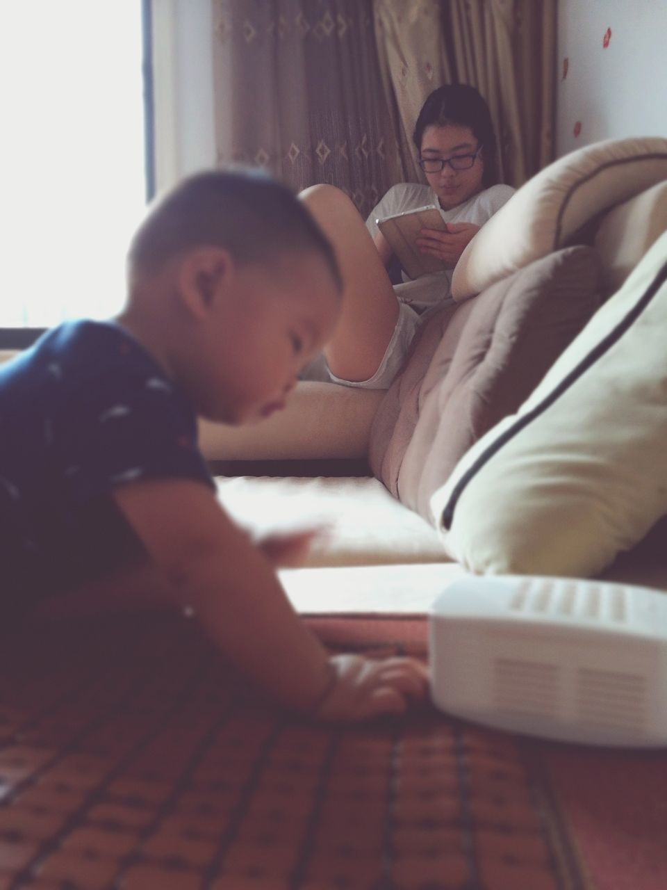 Boy By Sofa With Sister Using Digital Tablet In Living Room At Home