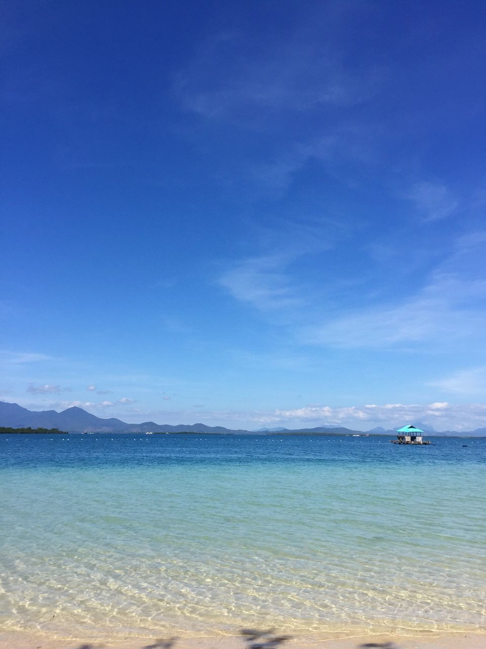 Scenic view of sea against blue sky on sunny day