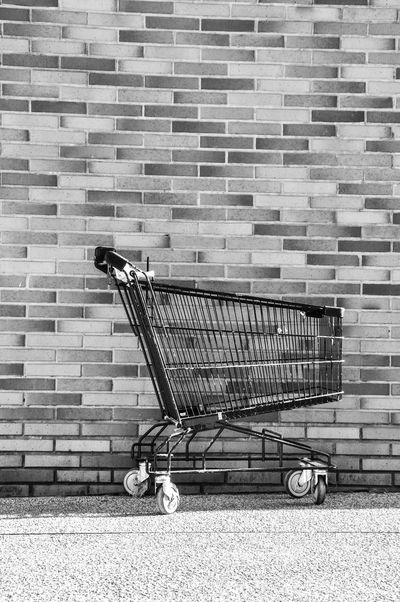 Architecture Brick Wall Building Exterior Consumerism Day No People Outdoors Shopping Cart Stationary Supermarket Trolley