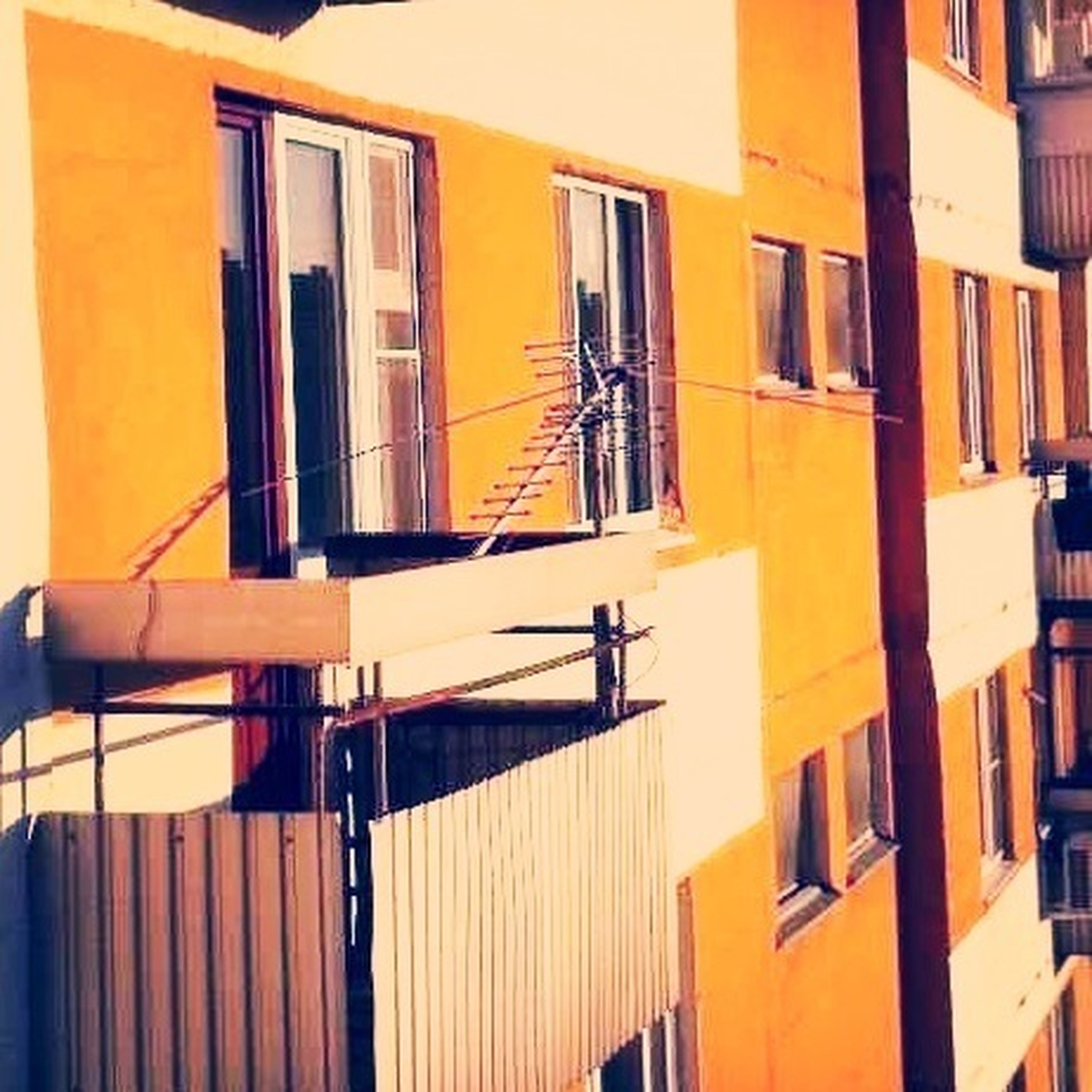 architecture, building exterior, built structure, window, residential building, residential structure, balcony, building, house, low angle view, apartment, yellow, city, railing, day, no people, outdoors, exterior, facade, in a row