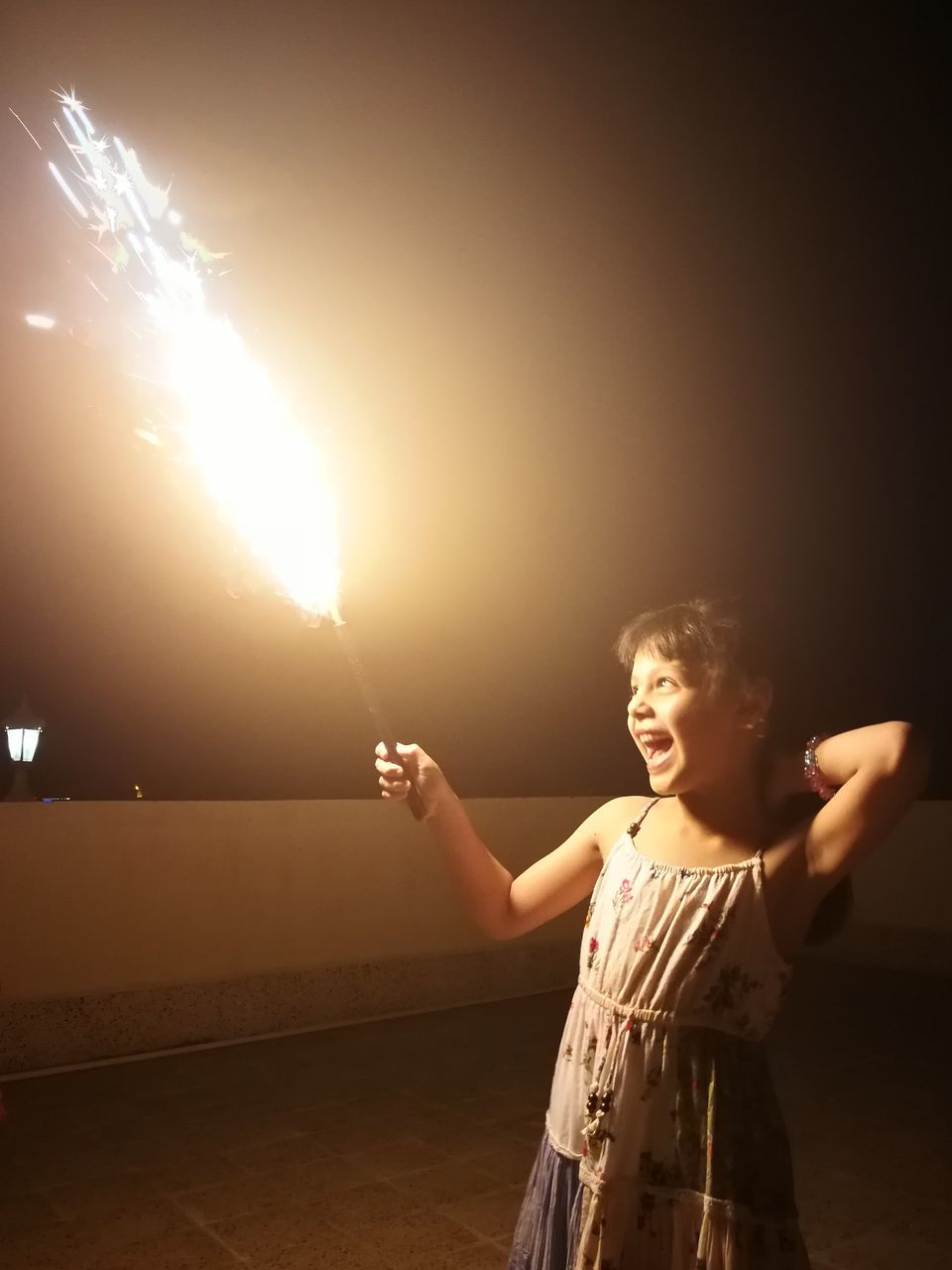 Girl Holding Firework While Standing On Building Terrace At Night