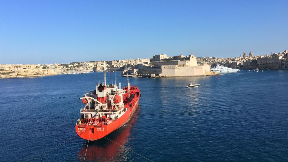 Grand Harbour View with red vessel in Valetta, Malta Architecture Blue Sea Blue Sky Building Exterior Built Structure Castle Clear Sky Day Grand Harbour Nature Nautical Vessel No People Outdoors Red Boat Sea Sky Transportation Water