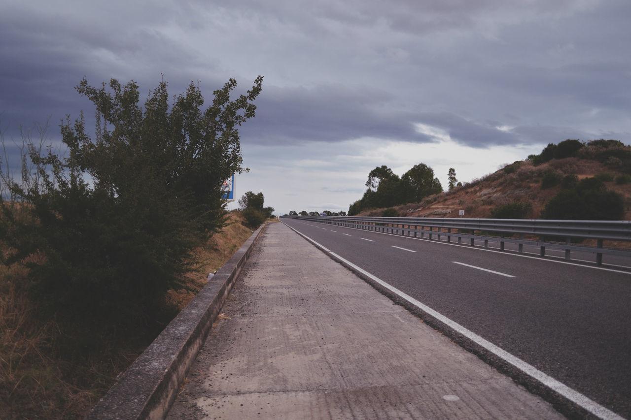 Sidewalk By Road Against Cloudy Sky