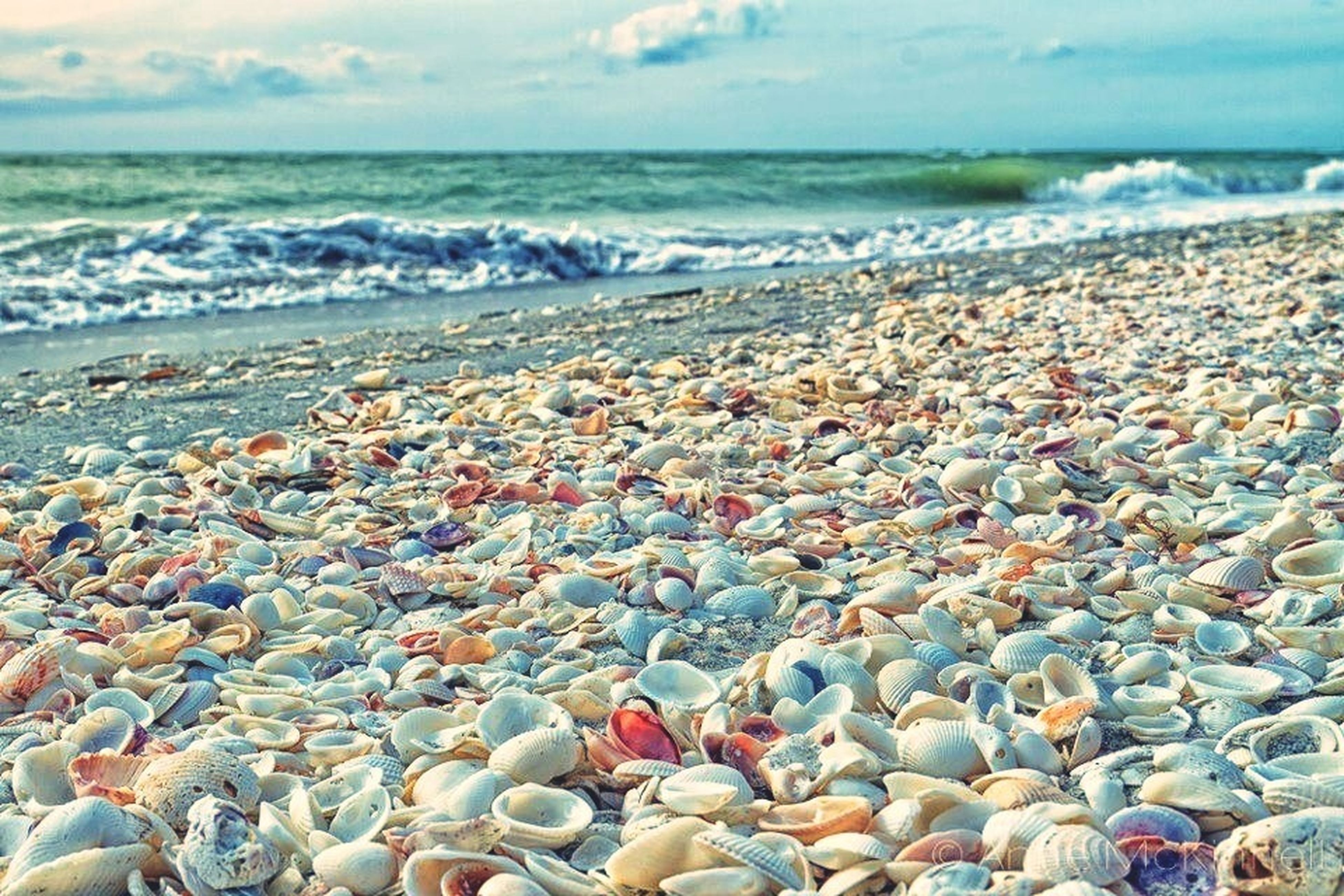 sea, horizon over water, water, beach, shore, sky, scenics, wave, beauty in nature, nature, surf, pebble, tranquility, vacations, stone - object, tranquil scene, coastline, rock - object, idyllic, cloud - sky
